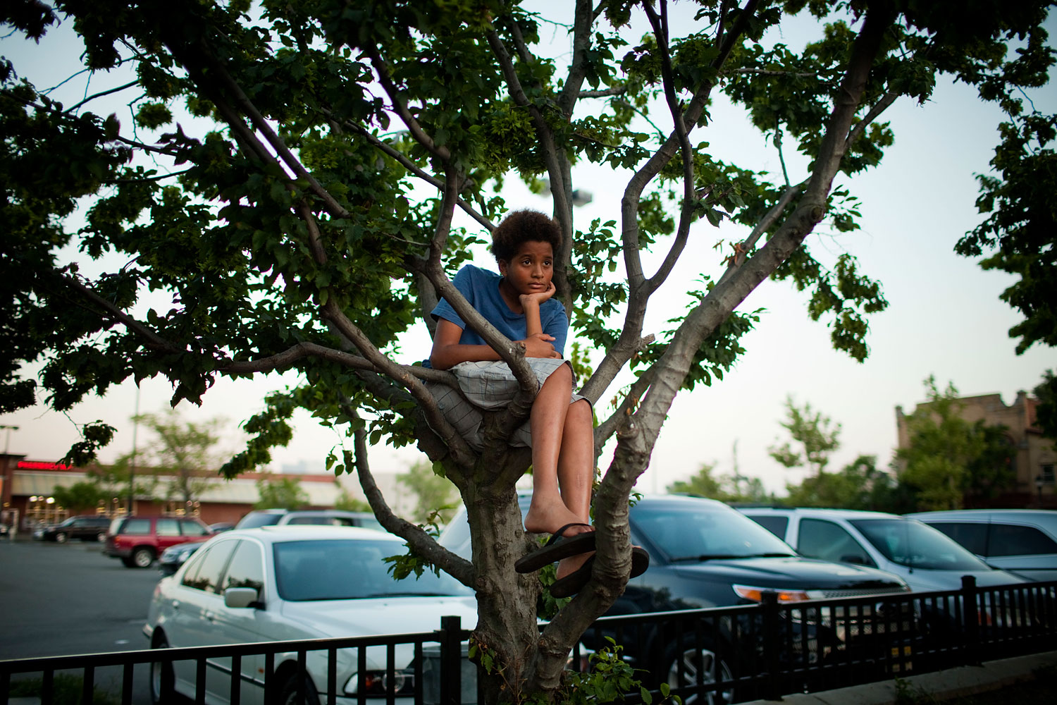 July 16, 2013. Dylan Strother, 13, of Jersey City, watches the crowd from a tree at the Hub Shopping Center where supporters of Trayvon Martin staged a rally in memory of Martin in Jersey City, N.J.