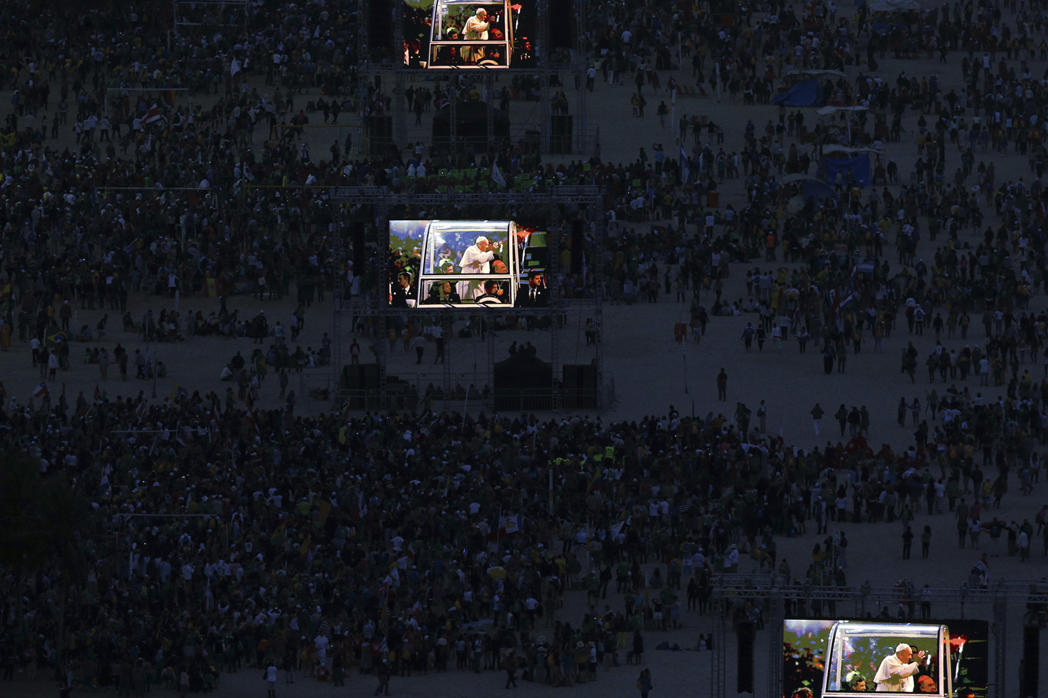 July 26, 2013. Pope Francis is projected on screens at Copacabana beach in Rio de Janeiro.