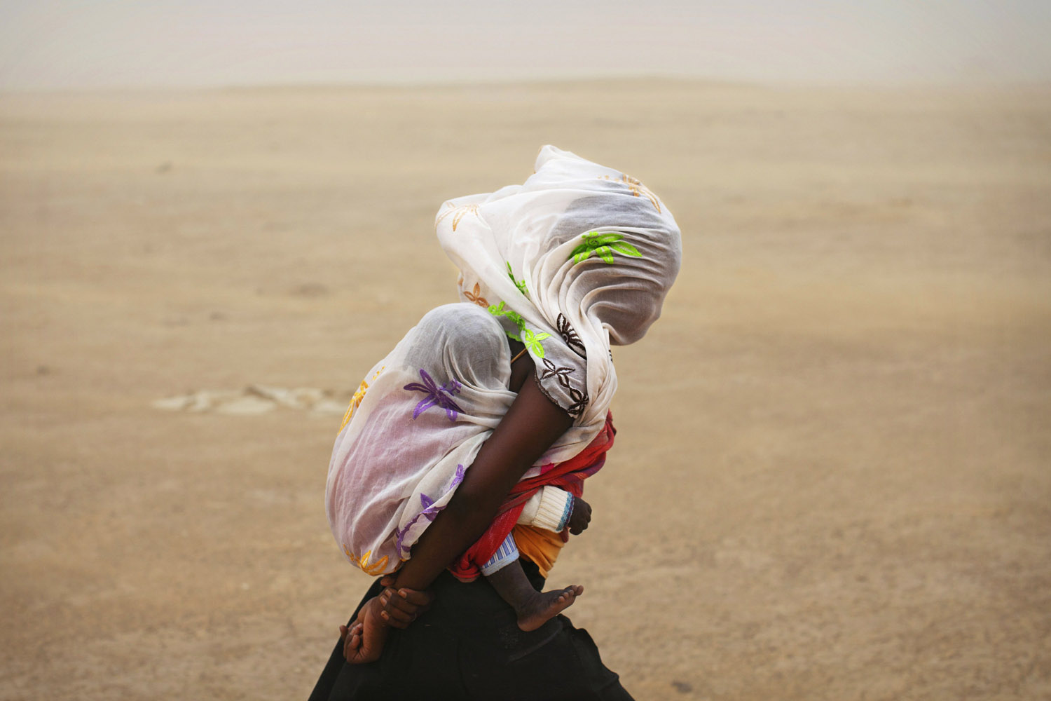July 29, 2013. A woman carrying her baby and wrapped with a shawl walks through a sandstorm in Timbuktu, Mali.
