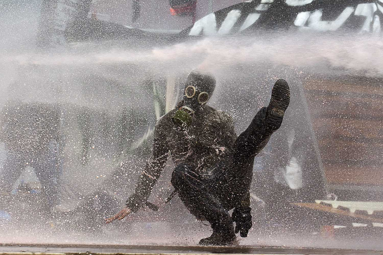 June 11, 2013. A protestor is hit by pressurized water sprayed from a riot police water cannon during clashes Taksim Square Istanbul, Turkey.