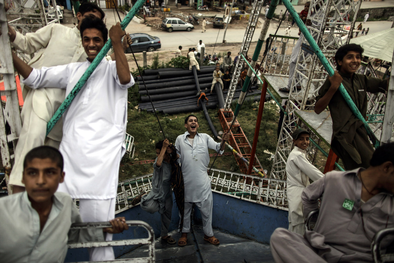 June 14, 2013. Pakistani youths enjoy a ride at a makeshift entertainment park set up outside a shrine in Rawalpindi, Pakistan.