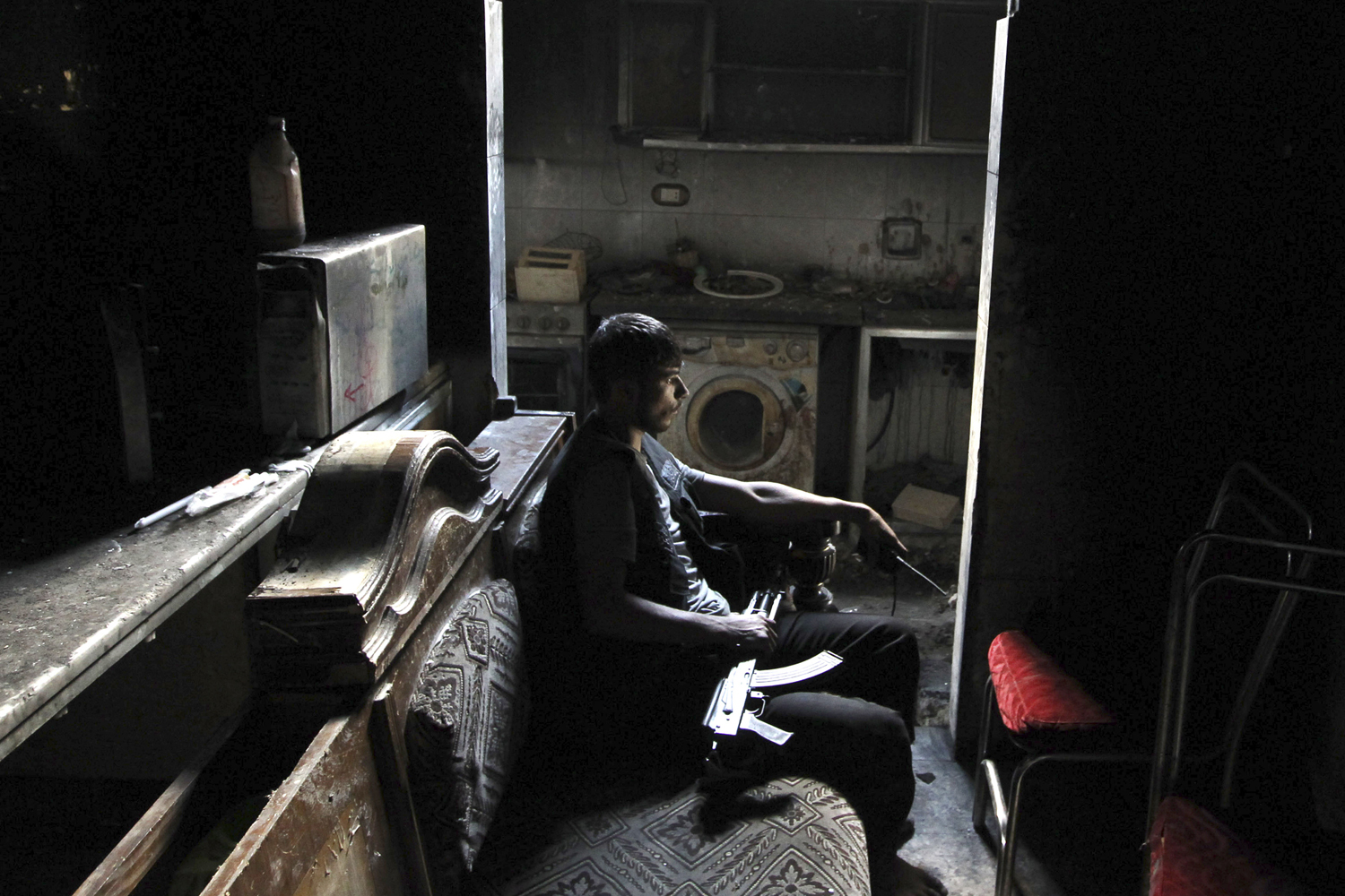 June 18, 2013. A member of the Free Syrian Army sits with his weapon inside a house in Aleppo's al-Sayyid Ali neighborhood.