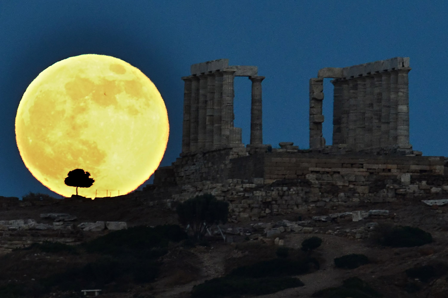 June 23, 2013. A supermoon rises next to the ancient Greek temple of Poseidon at Cape Sounion, some 65 kilometers south of Athens.
