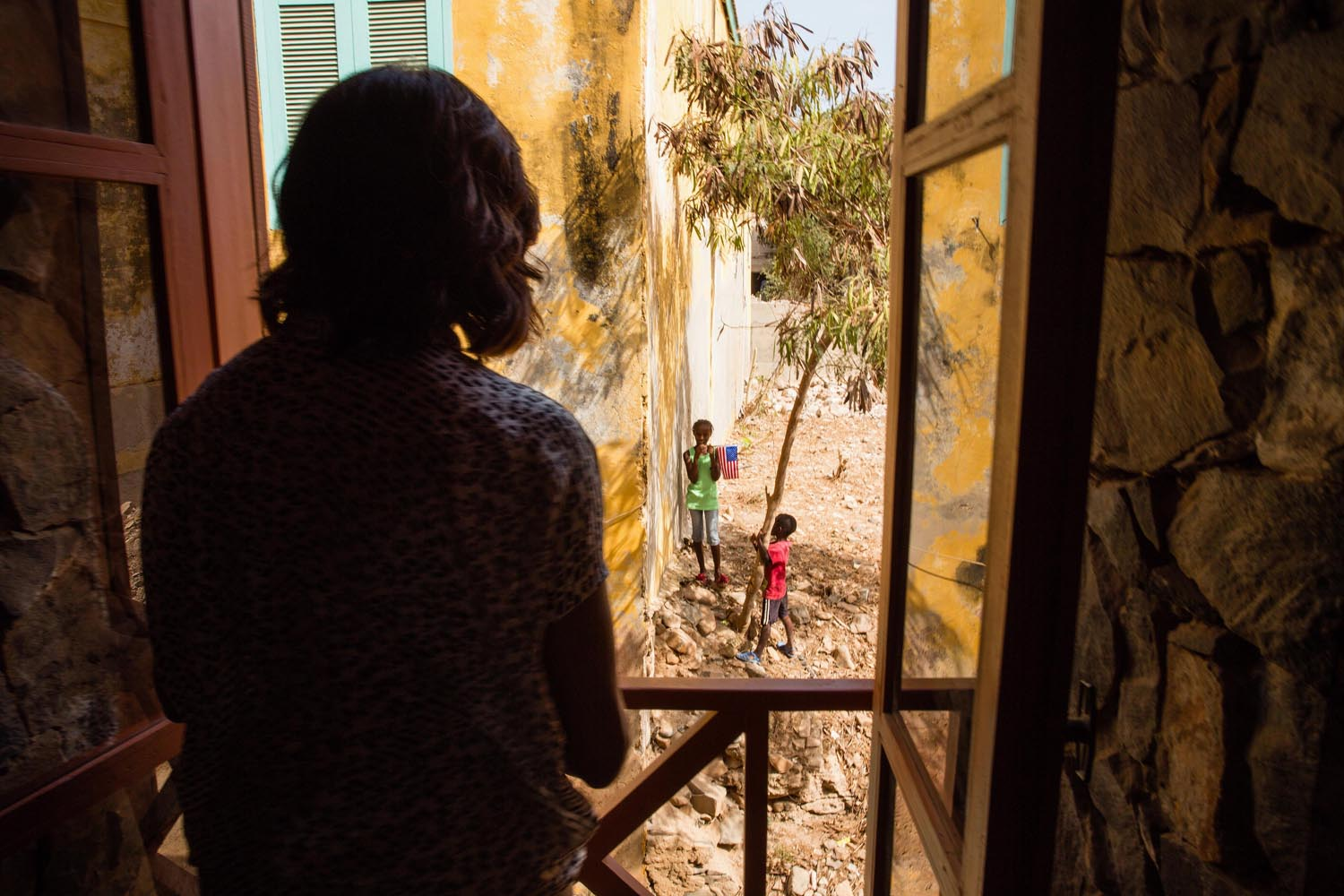 June 27, 2013. First Lady Michelle Obama looks out a window at local children during her visit to a cultural center on Gorée Island, Senegal.
