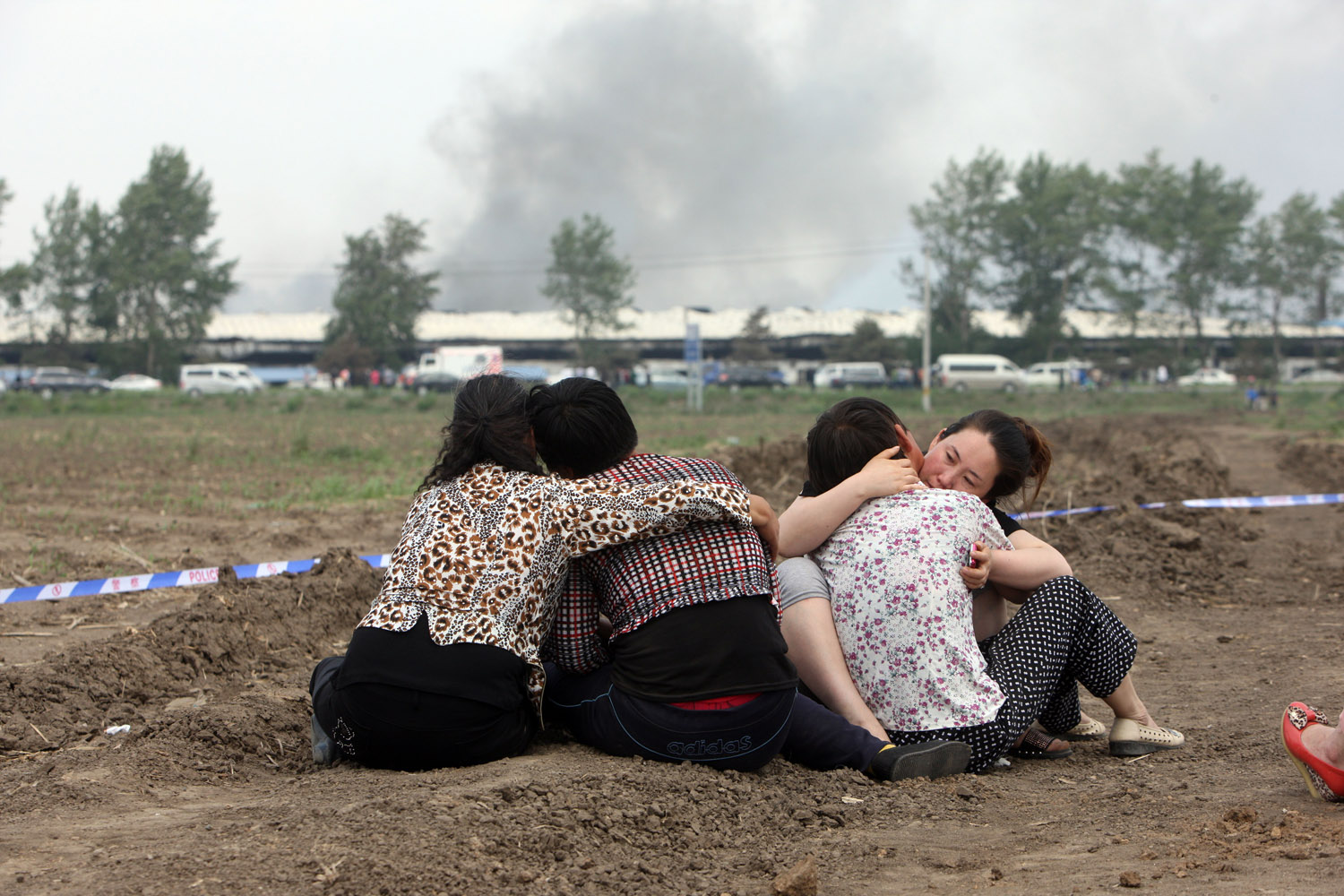 June 3, 2013. Victims' relatives are seen at the scene after a fire that killed 119 and injured 54 people at a locked poultry slaughterhouse in Dehui, northeast China's Jilin province.
