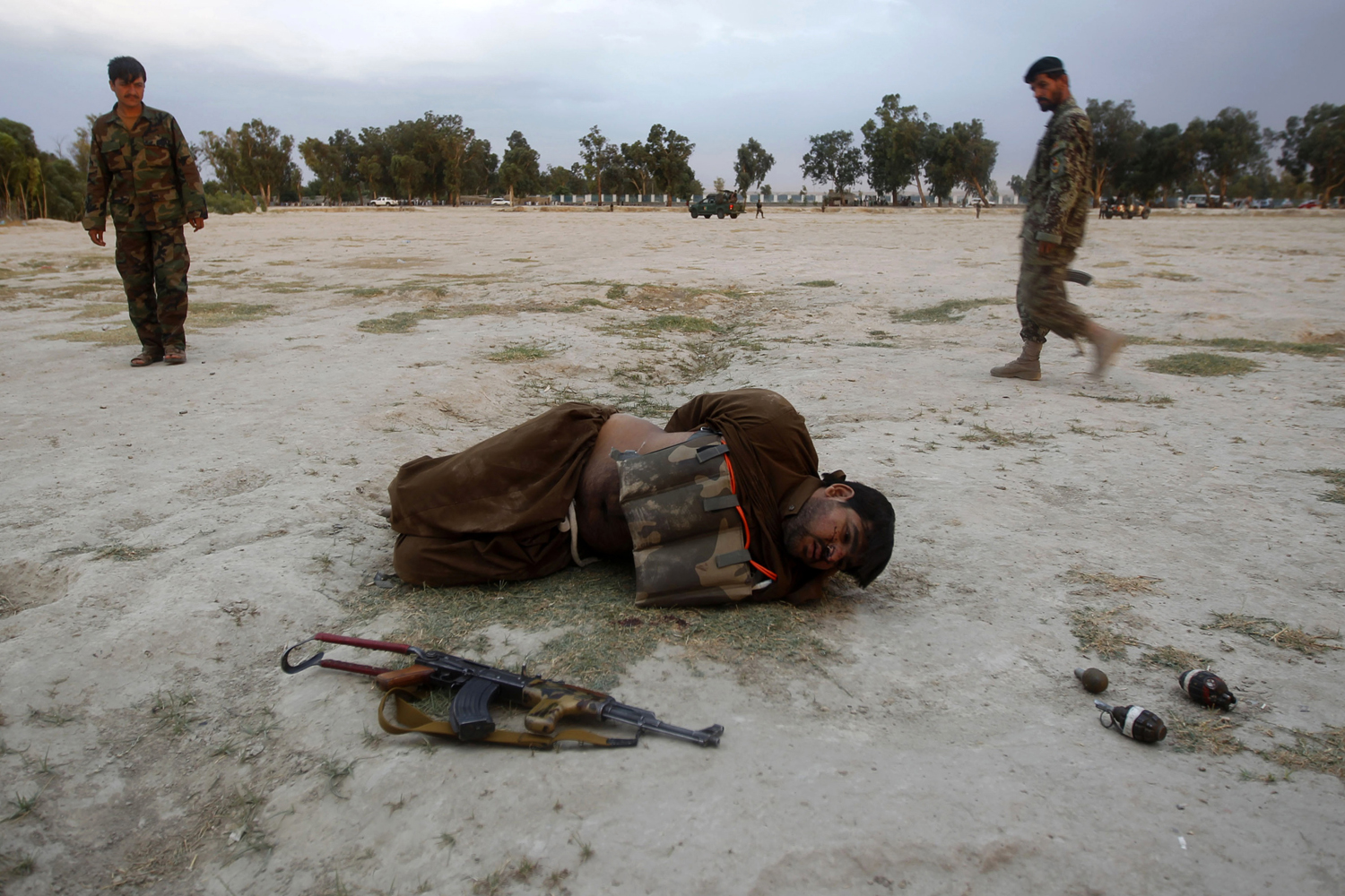 June 30, 2013. Afghan National Army (ANA) soldiers approach a captured would-be suicide attacker after his vest was defused in Jalalabad province.