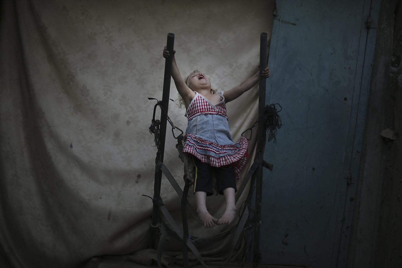 June 5, 2013. A Palestinian refugee girl plays inside her family home in Jabaliya refugee camp, northern Gaza Strip.