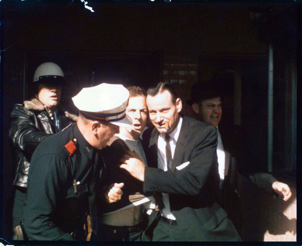 Lee Harvey Oswald is dragged from the Texas Theatre by Patrolman C.T. Walker and, still chewing his cigar, Detective Paul Bentley, on Nov. 22, 1963. On the right right is Sgt. Gerald Hill.