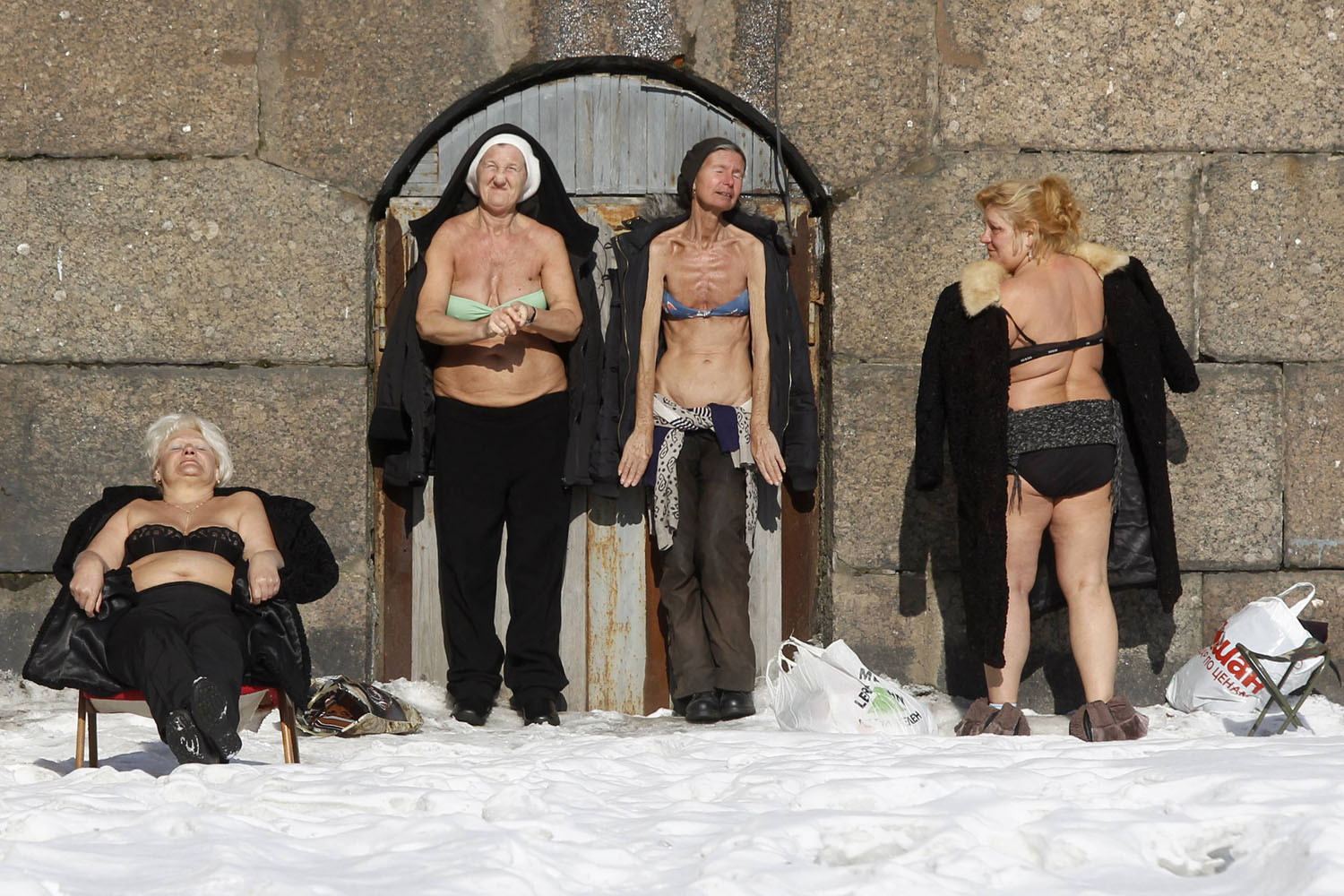 March 10, 2013. People sunbathe by the wall of the Peter and Paul Fortress in St. Petersburg, Russia.