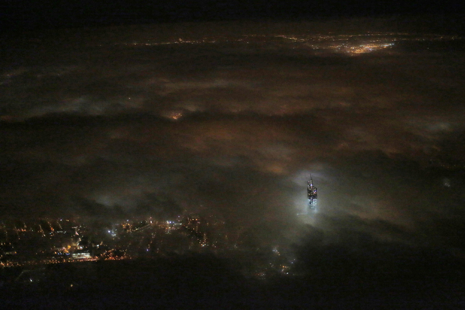 March 12, 2013. One World Trade Center emerges from the clouds in the night sky in a photo made from a passing airplane in New York.