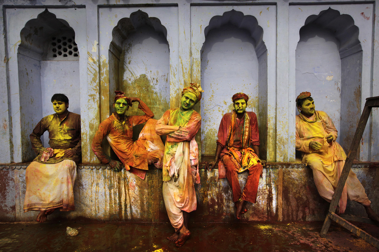 March 22, 2013. Indian villagers from Nandgaon wait for the arrival of villagers from Barsana to play Lathmar Holi at the Nandagram temple famous for Lord Krishna and his brother Balram, in Nandgaon, 120 kilometers ( 75 miles) from New Delhi, India.