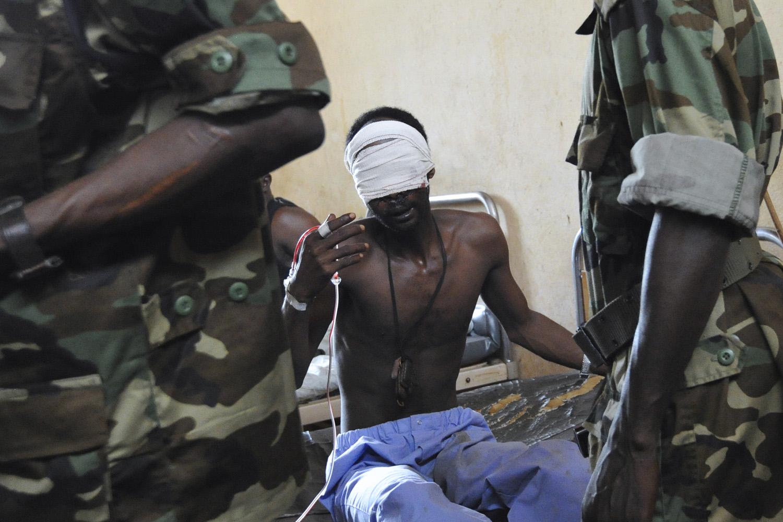 March 29, 2013. Central African Seleka rebels speak to an injured Seleka rebel at a community hospital in Bangui.