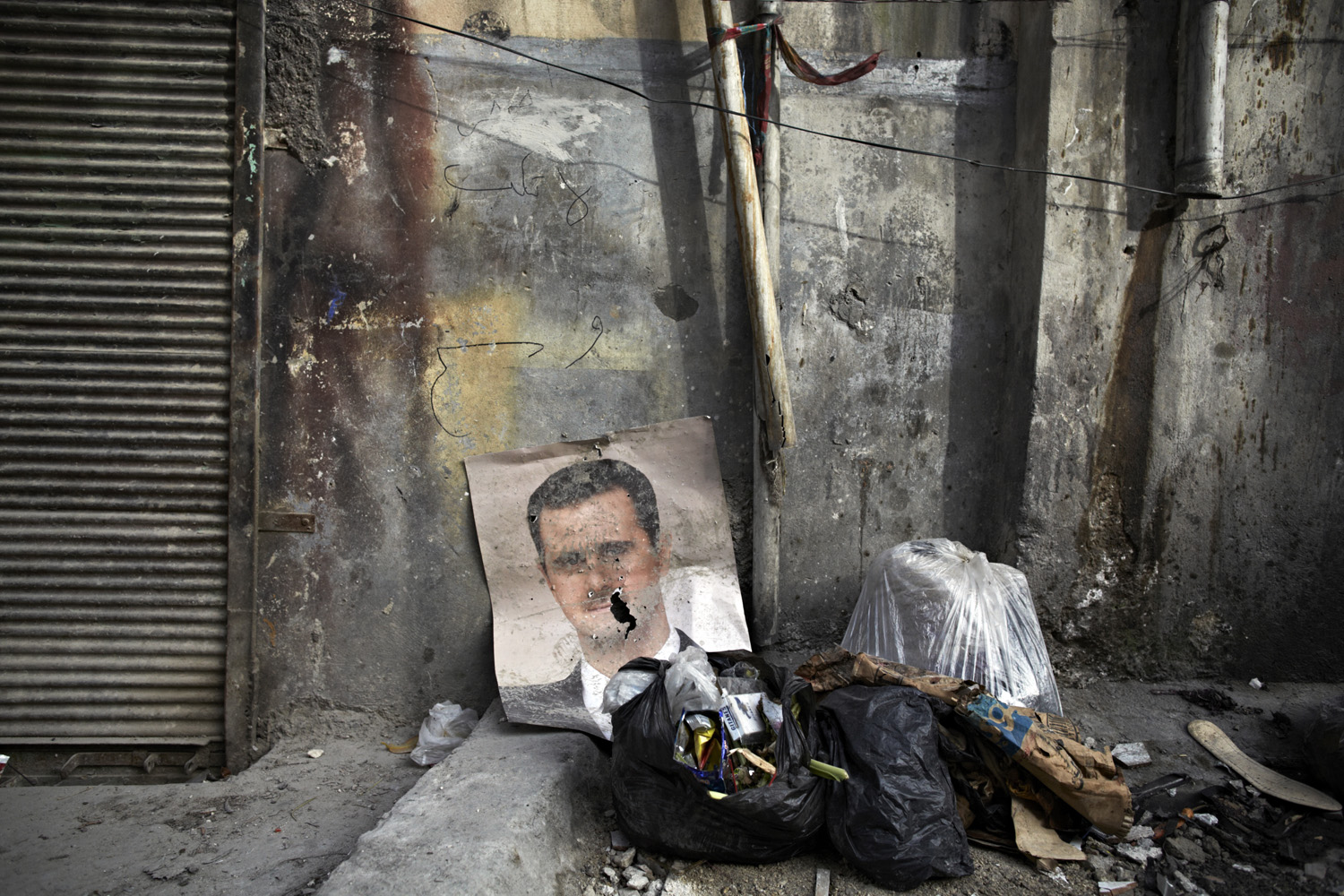 March 30, 2013. The bullet-riddled poster of Syria's current president in the newly liberated neighborhood of Sheikh Maksoud in Aleppo, Syria.