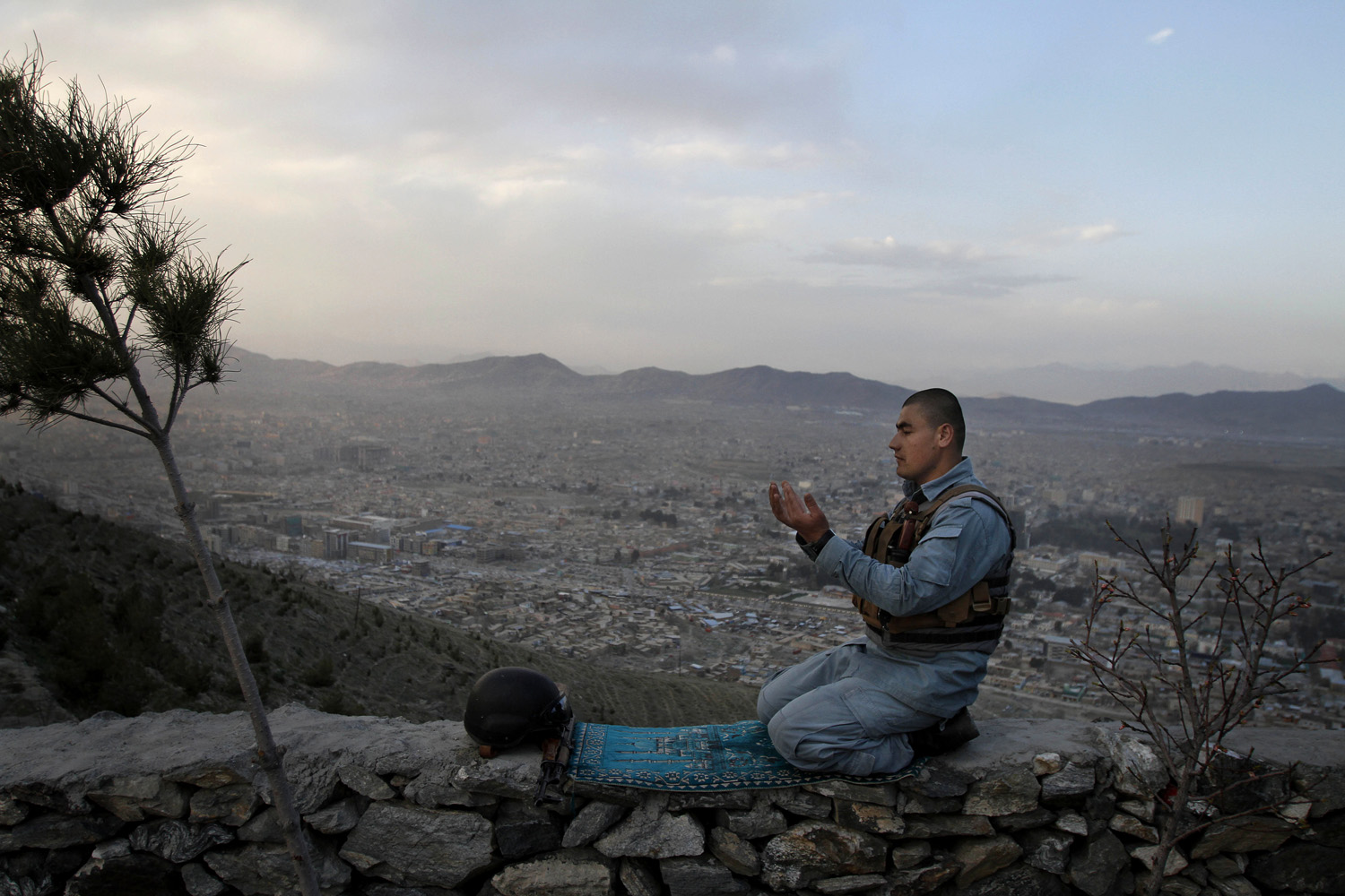 March 31, 2013. An Afghan police man offers evening prayers on a hill overlooking Kabul, Afghanistan.