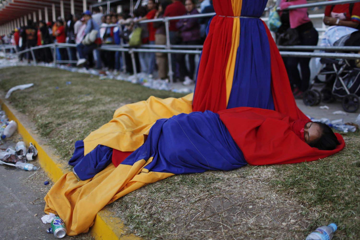 March 8, 2013. A woman wrapped in cloths decorating a light post in the colors of Venezuela's flag sleeps outside the military academy where a funeral ceremony will take place for Venezuela's late President Hugo Chavez in Caracas, Venezuela.