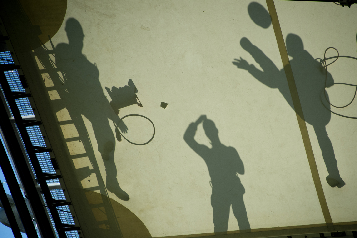 May 15, 2013. Workers are silhouetted on the roof as they play with a helmet during the visit of the FIFA Secretary General Jerome Valcke at the Maracana stadium in Rio de Janeiro, Brazil.