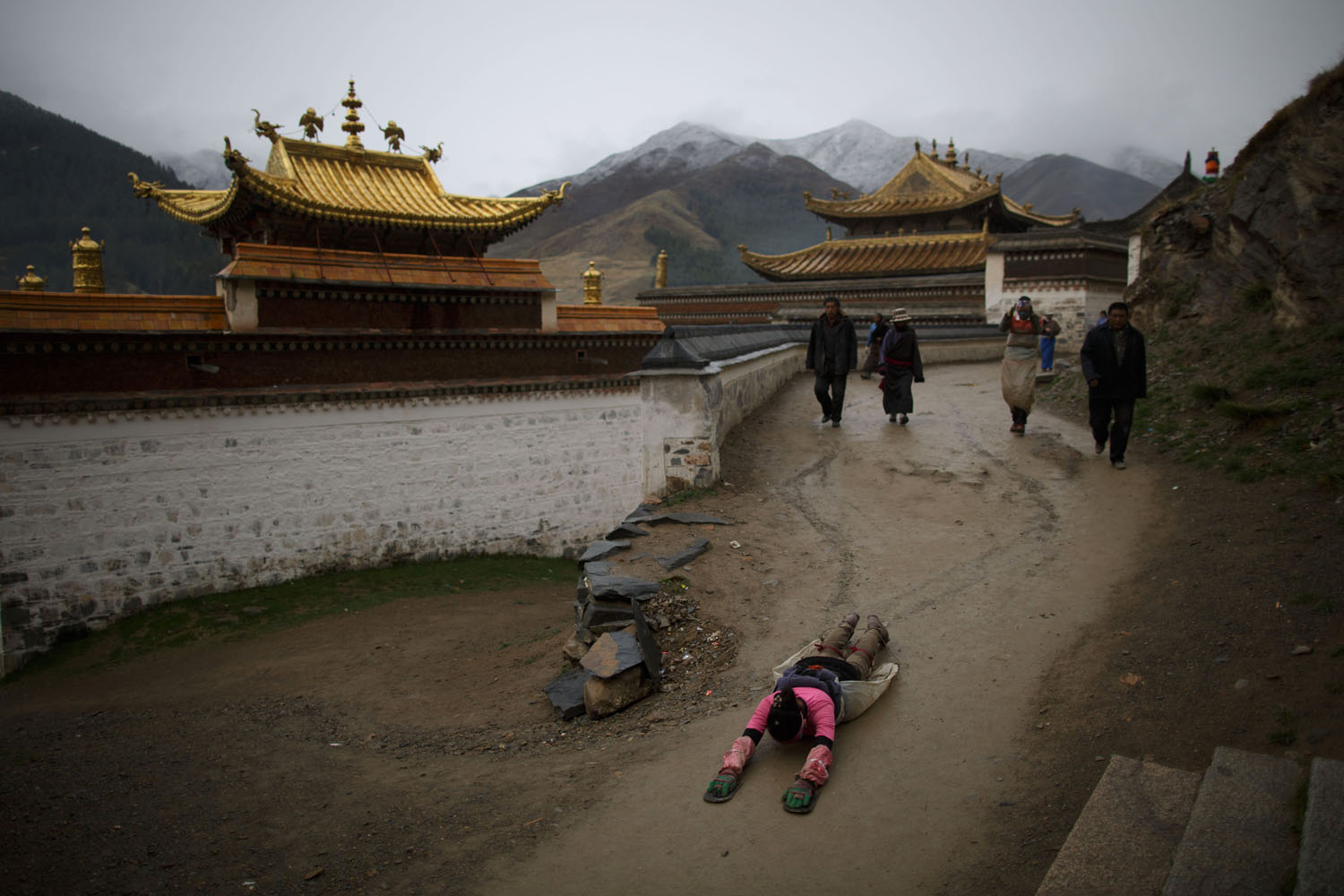 May 17, 2013. A Tibetan woman (bottom) prostrates near Labrang monastery in Xiahe, Gansu province, a flashpoint for many Tibetan protests against Chinese authorities.