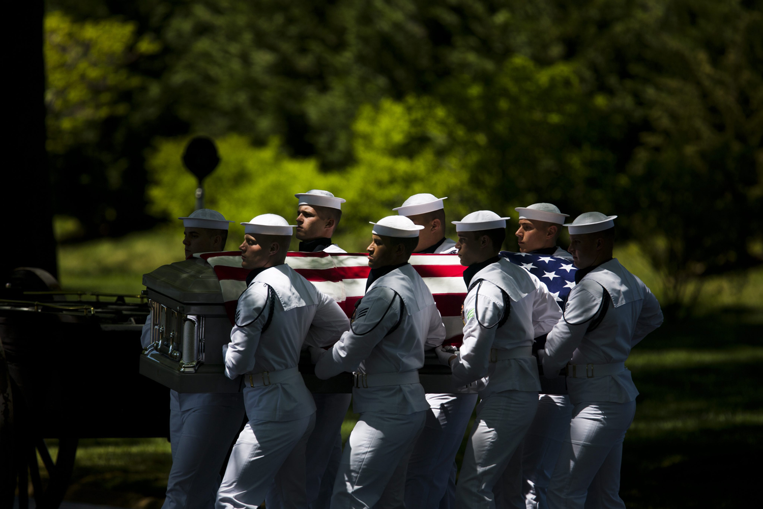 May 2, 2013. At a group burial service at Arlington National Cemetery, a U.S. Navy honor guard team carries the remains of four sailors, Lieutenant Dennis Peterson, Ensign Donald Frye, Aviation Antisubmarine Warfare Technician William Jackson, and Aviation Antisubmarine Warfare Technician Donald McGranein, all missing since the Vietnam War, in Arlington, Virginia.