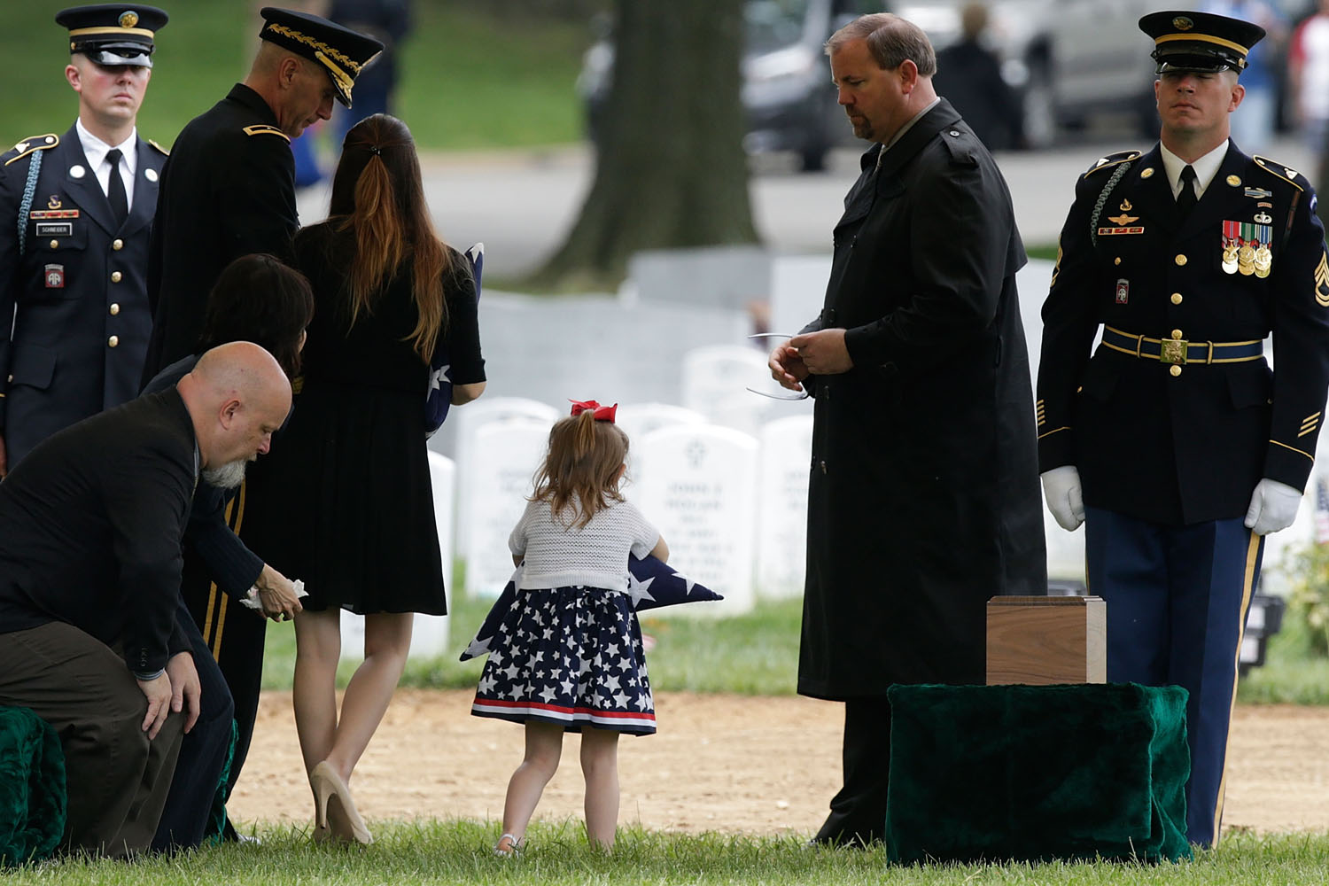 May 20, 2013. Four-year-old Sophia Phillips carries an American flag presented to her during a burial service for her father, Staff Sergeant Francis G. Phillips, at Arlington National Cemetery in Arlington Va.