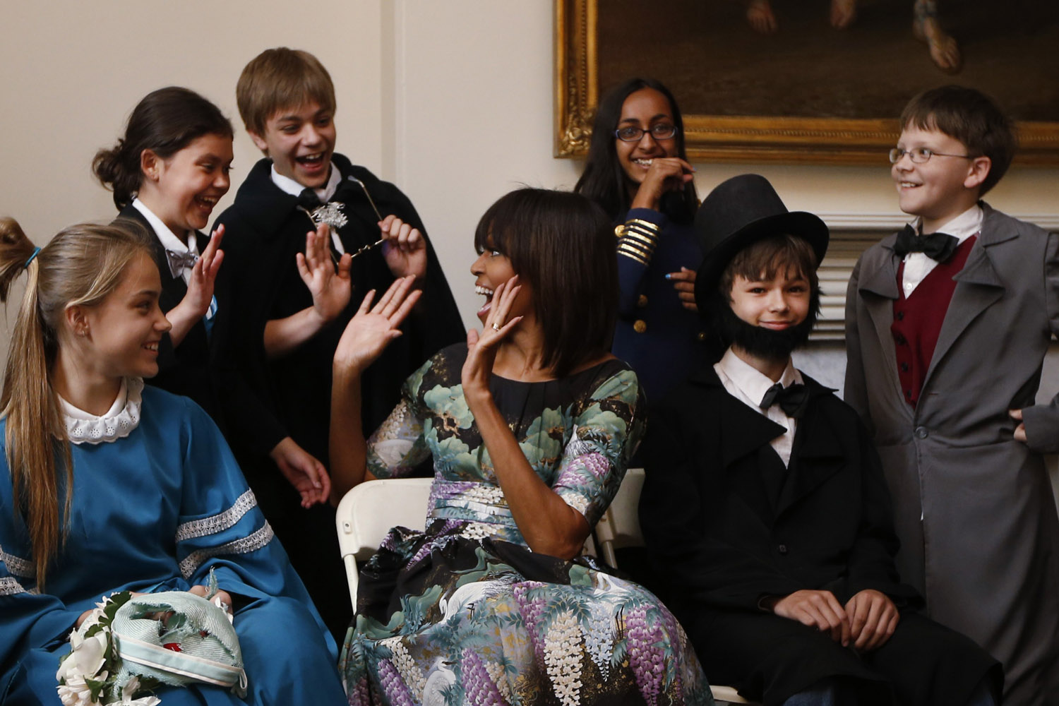 May 22, 2013. U.S. first lady Michelle Obama reacts with school children from Willow Springs Elementary School in Fairfax, Va, as they participate in a play about the emancipation of slaves during Abraham Lincoln's presidency, at historic Decatur House in Washington.
