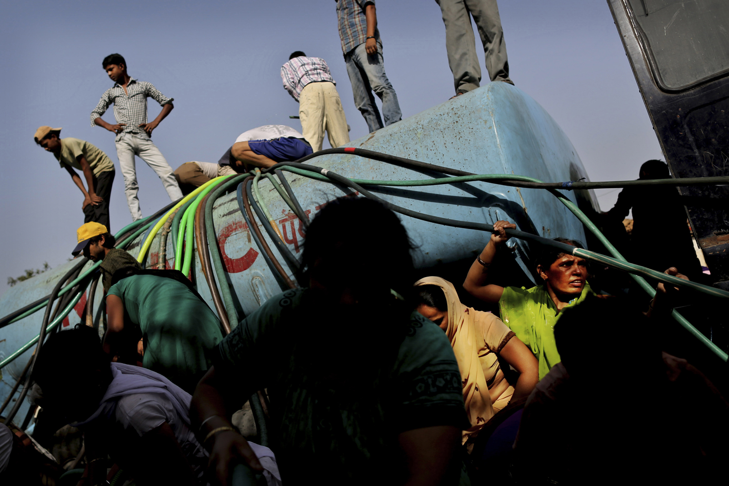 May 23, 2013. Indian people stand on a government tanker as others struggle with hoses to collect drinking water from the tanker because of short supply in running water taps at a slum in New Delhi, India.