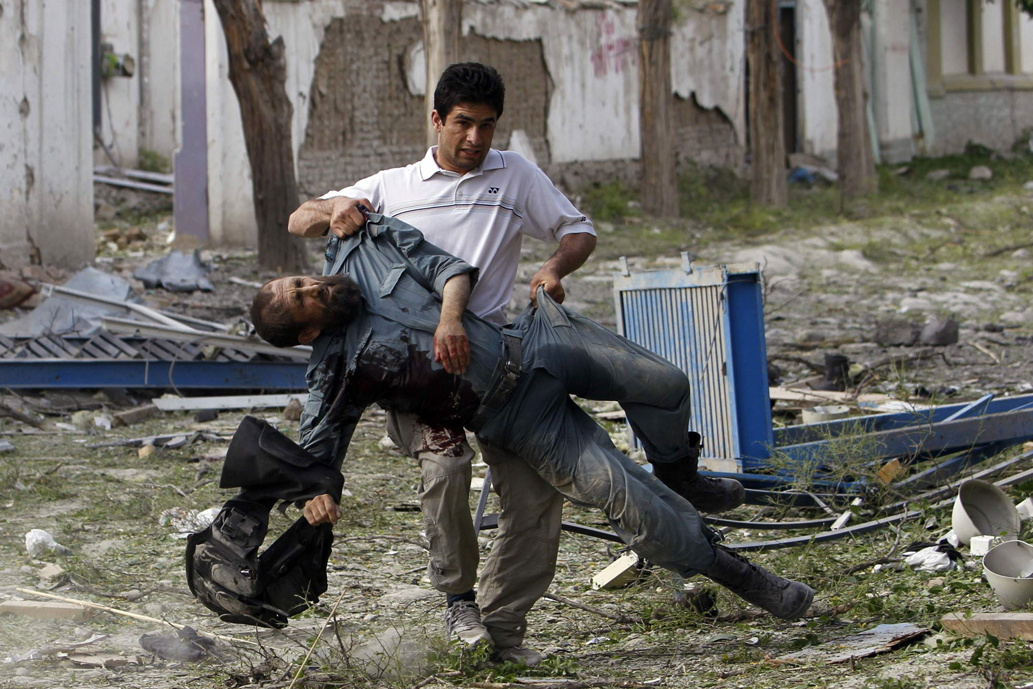 May 24, 2013. A wounded Afghan policeman is carried away from the site of an explosion in Kabul.
