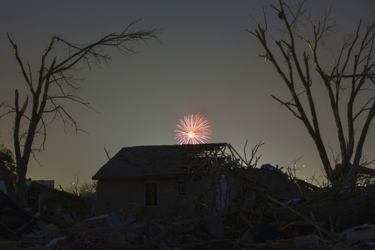 May 26, 2013. Memorial day fireworks explode over a house damaged by the May 20 afternoon tornado in Moore, Okla.