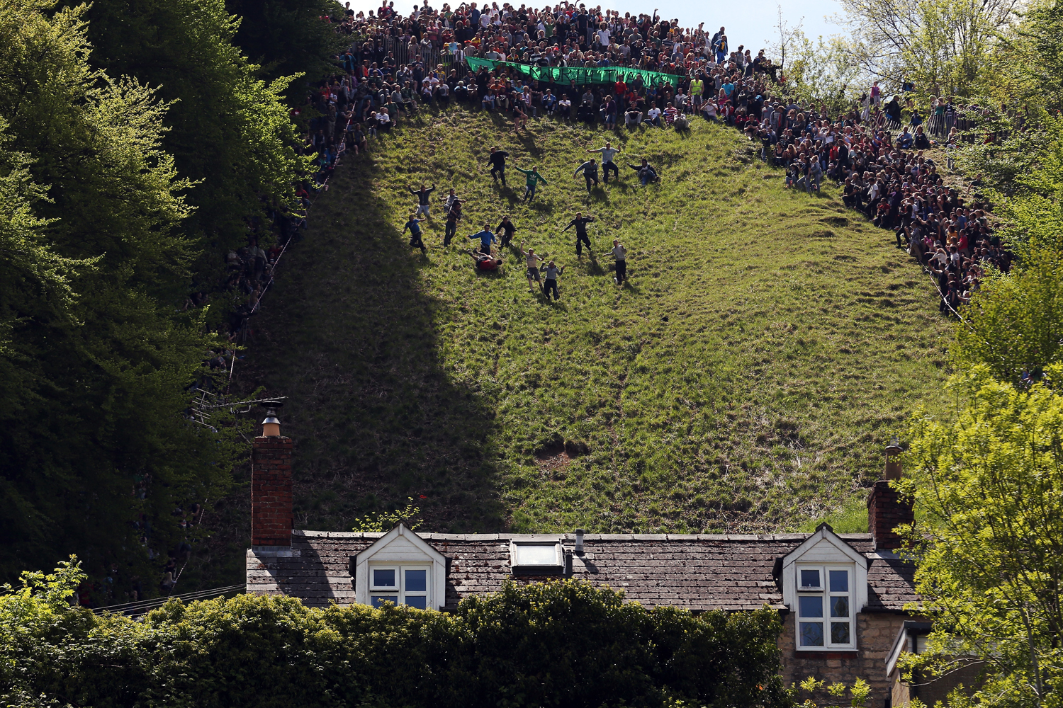 May 27, 2013. Contestants in the men's race chase a replica Double Gloucester Cheese down the steep gradient of Cooper's Hill during the annual Bank Holiday tradition of cheese-rolling in Brockworth, Gloucestershire, England.