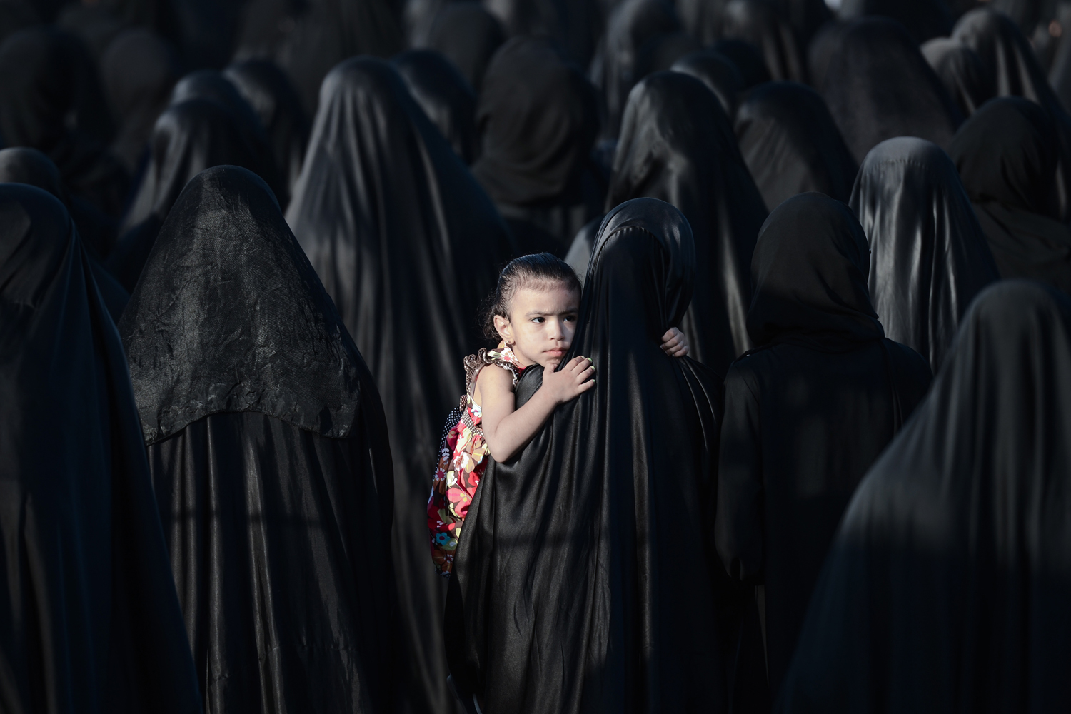 May 28, 2013. A Bahraini girl is carried by her mother during the funeral of Sayed Omran Sayed Hameed, in the village of Karzakkan, south of Manama.