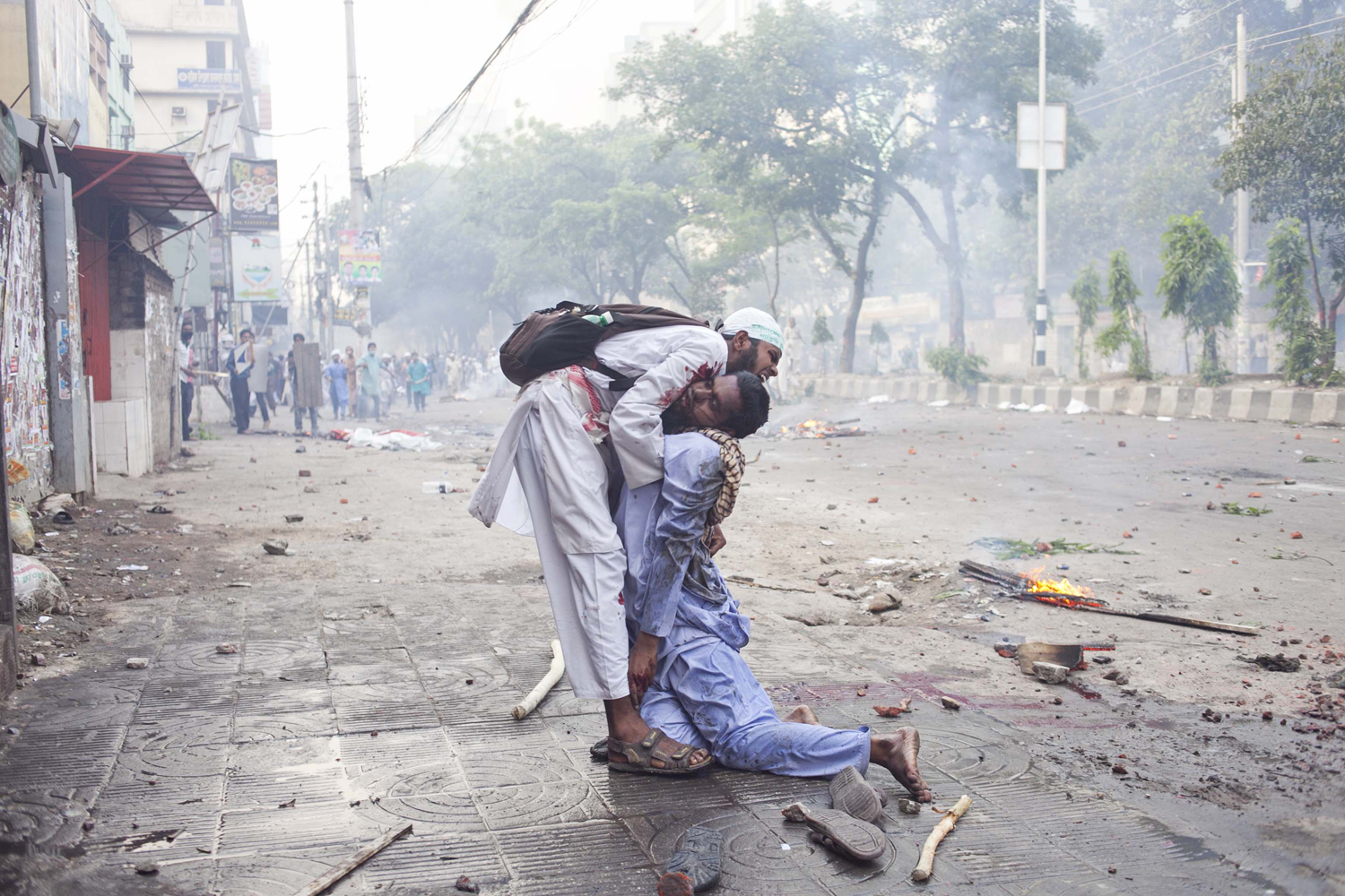 May 5, 2013. An activist tries to take another severely injured activist to the hospital, as no one else offers to help, in Dhaka, Bangladesh.