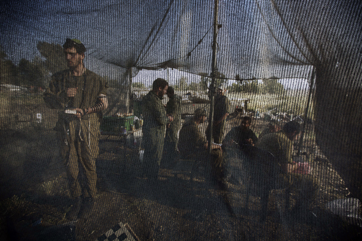 May 6, 2013. An Israeli soldier (L) prays inside a net tent pitched close to Merkava tanks deployed in the Israeli annexed Golan Heights near the border with Syria.