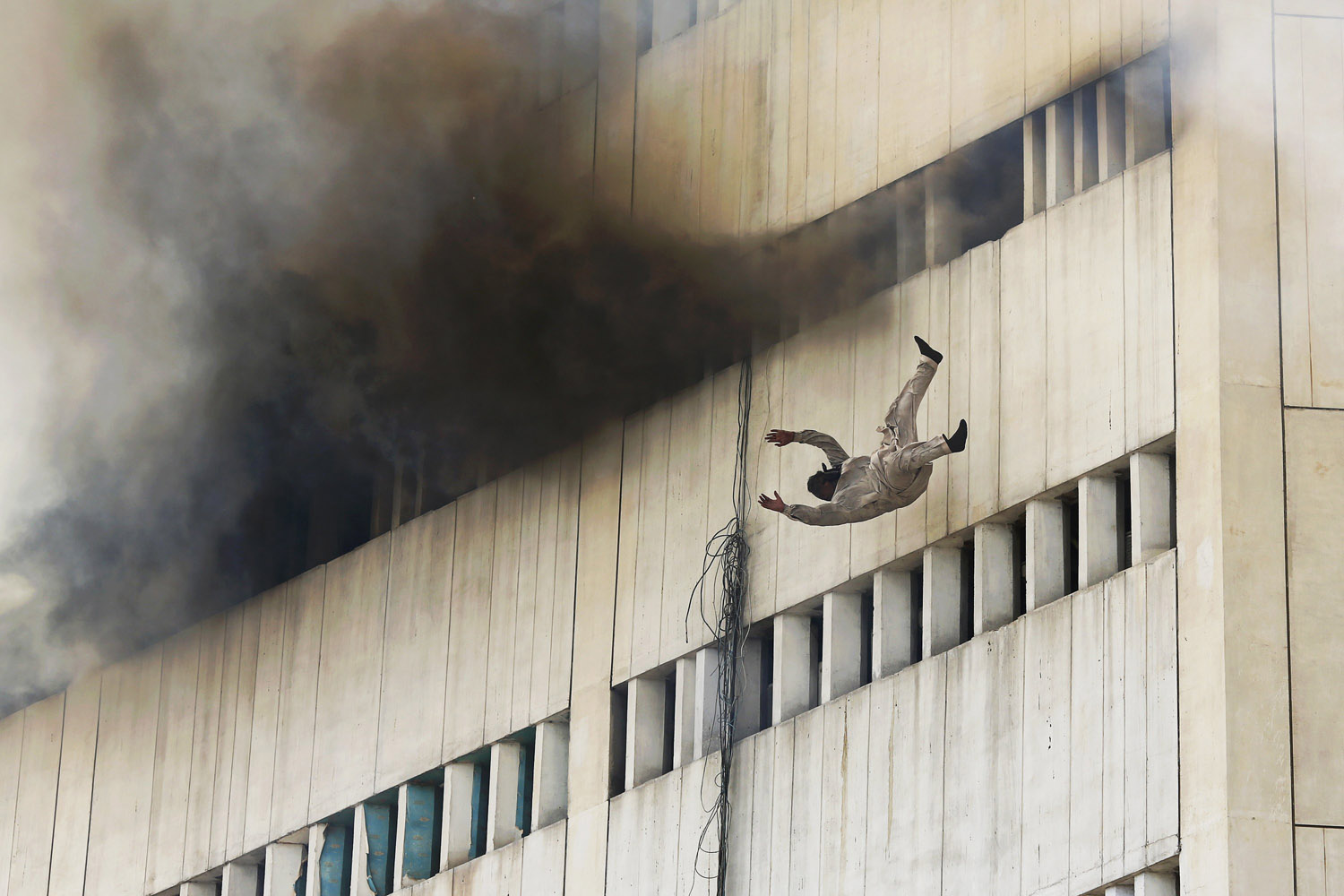 May 9, 2013. A man falls from a high floor of a burning building in central Lahore, Pakistan.