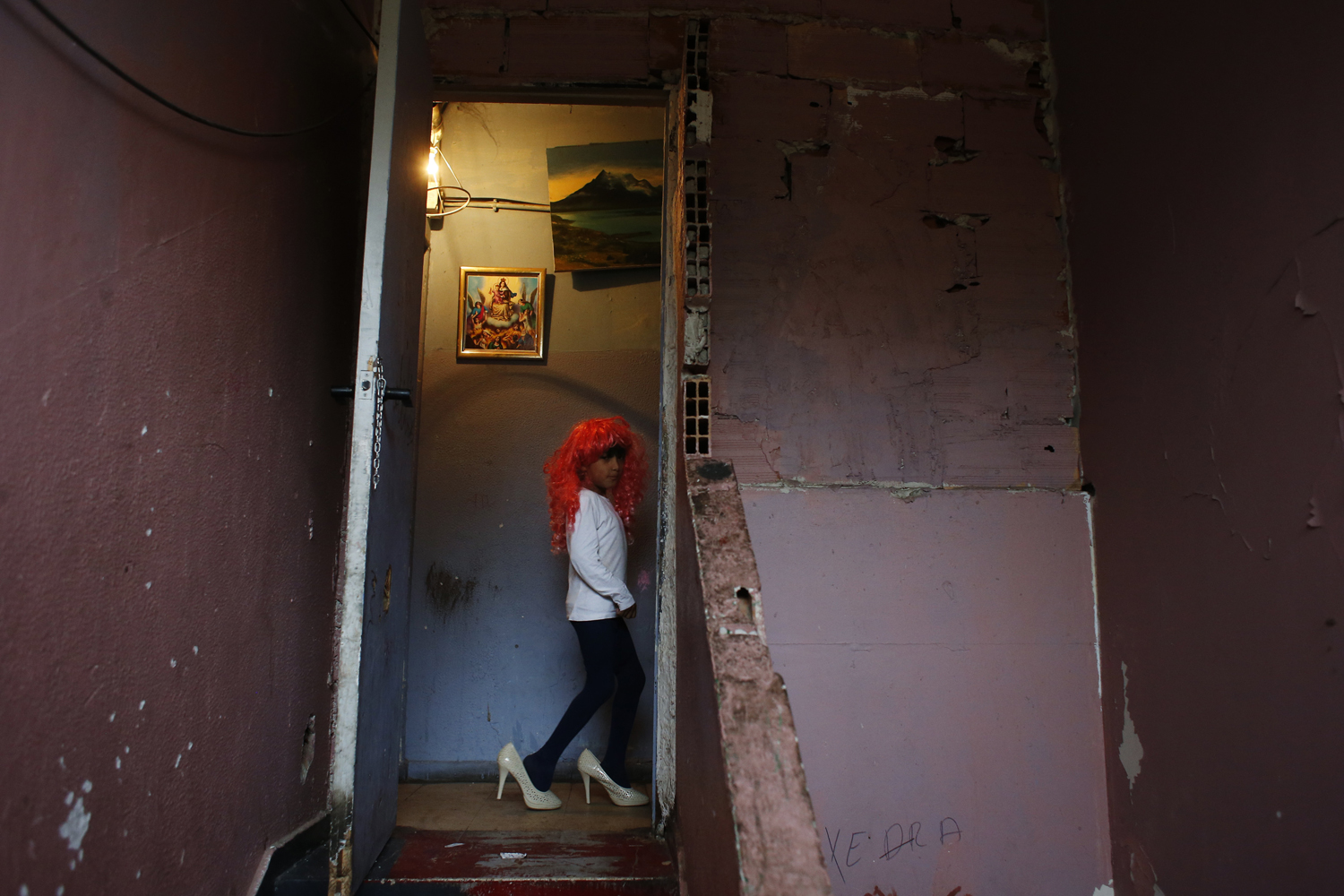 Nov. 7, 2013. Antonio Acuna, 7, plays dress up with a wig and high heel shoes at the factory where he lives with his family after the postponement of the demolition of their homes in Madrid.
