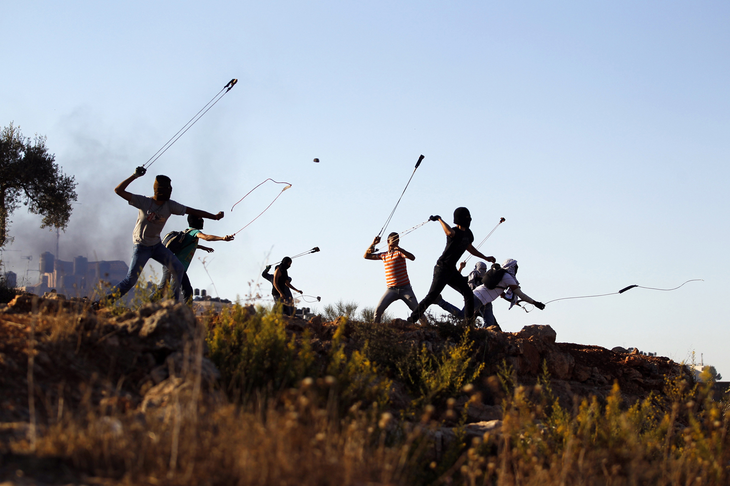Oct. 11, 2013. Palestinian protesters hurl rocks at Israeli soldiers during clashes in Betunia, near the West Bank city of Ramallah.