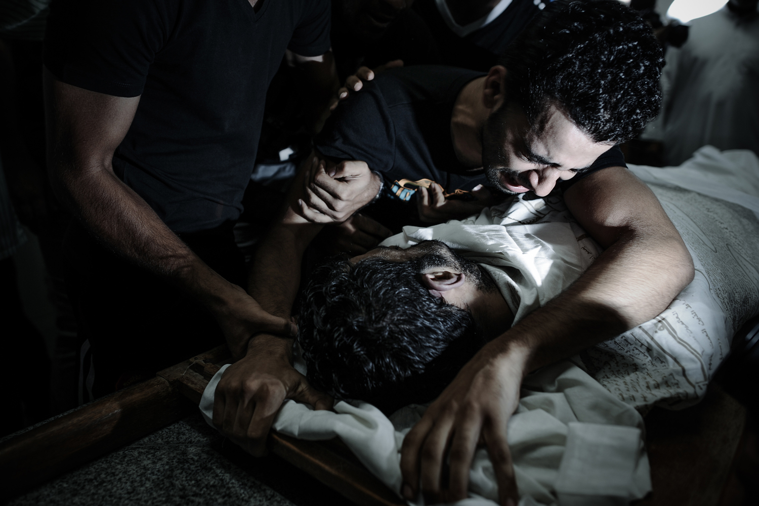 Oct. 12, 2013. The brother of Yussef al-Nashmi, who died in hospital the day before as he was detained by Bahraini authorities since August 17, mourns over his body during his funeral in the western Manama suburb of Jidd Hafs.