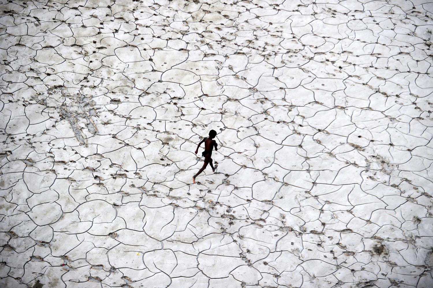 Oct. 25, 2013. An Indian street child plays in a dry river bed after flood waters receded in Allahabad, India.