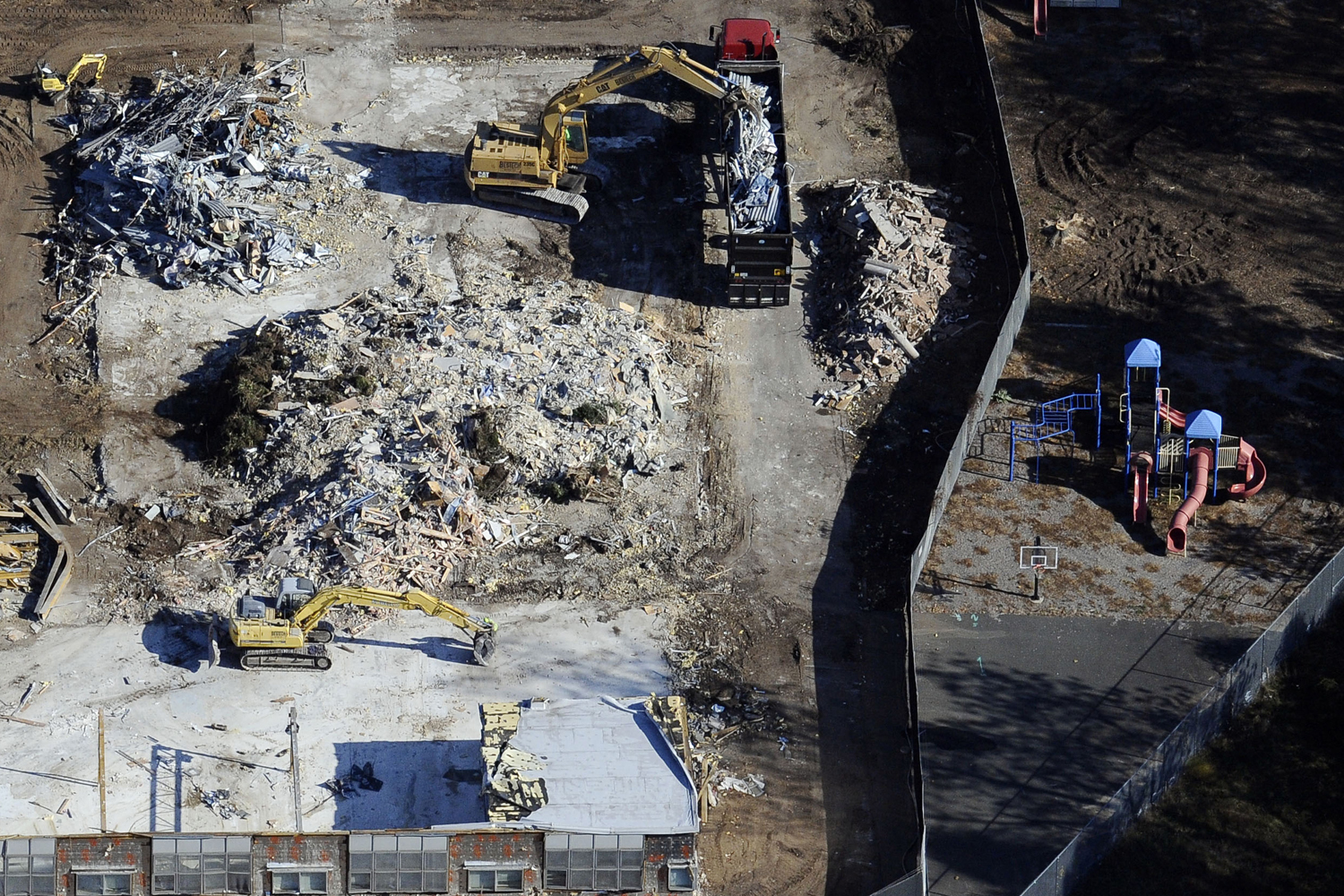 Oct. 28, 2013. Workers use backhoes to dig through the rubble as the demolition of Sandy Hook Elementary School continues, in Newtown, Conn.