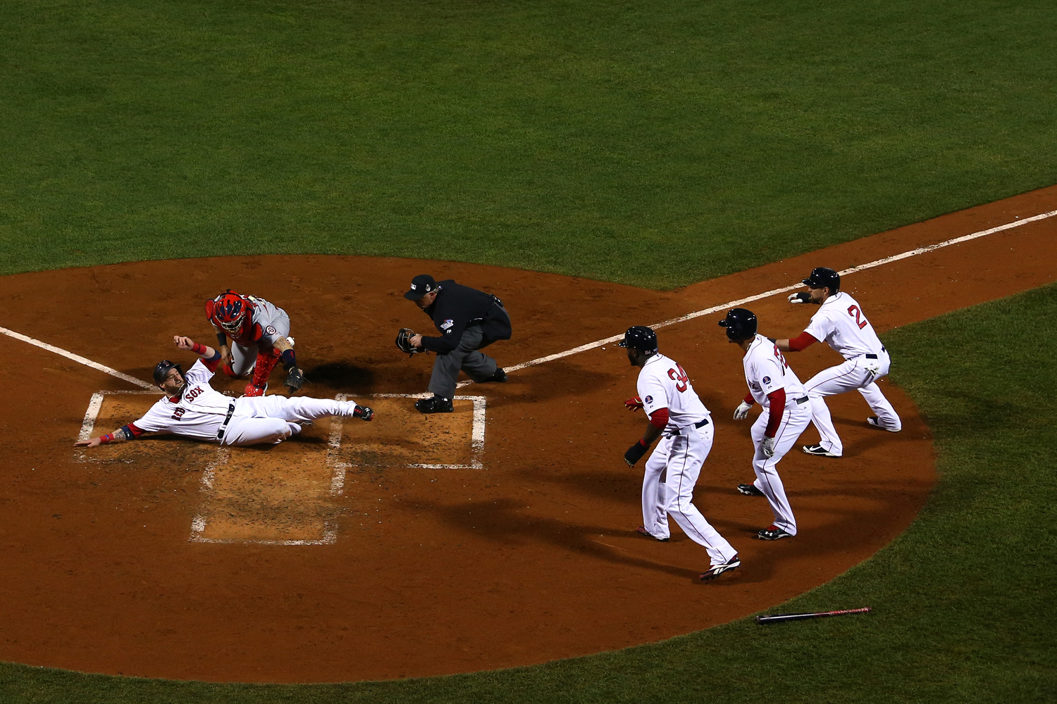 Oct. 30, 2013. Jonny Gomes #5 of the Boston Red Sox slides safely into home plate as Yadier Molina #4 of the St. Louis Cardinals tries to make the play during Game Six of the 2013 World Series at Fenway Park in Boston, Mass.