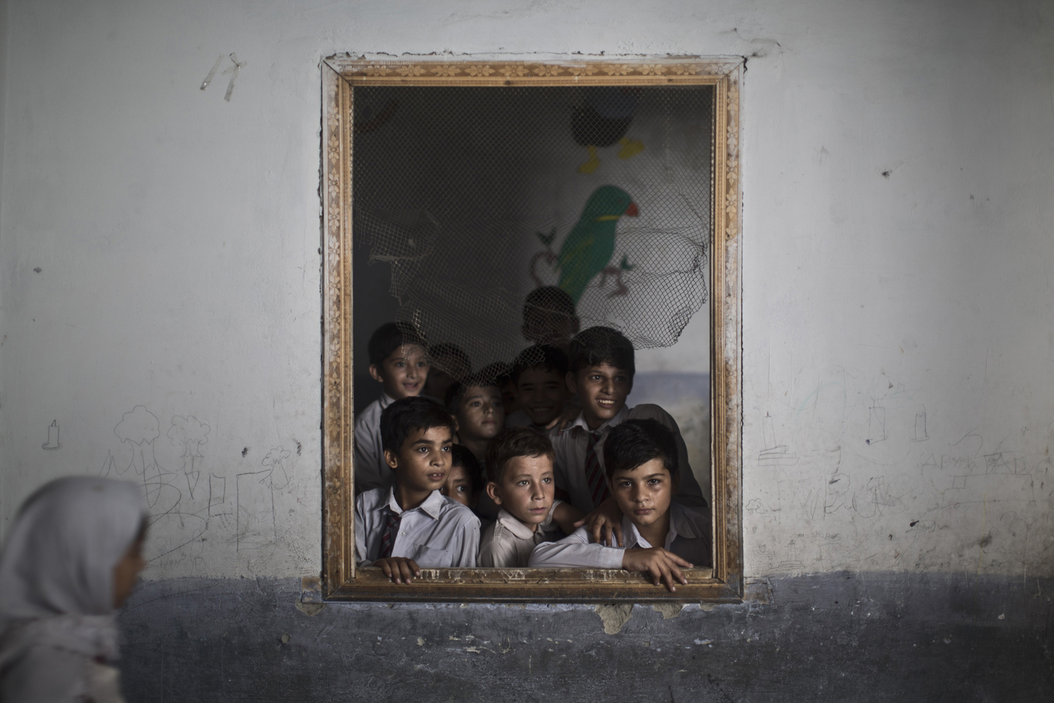 Oct. 9, 2013. Pakistani schoolboys look out the window of their classroom at other classmates chanting prayers to commemorate the anniversary of Malala's shooting by Taliban, at a school in Rawalpindi, Pakistan.