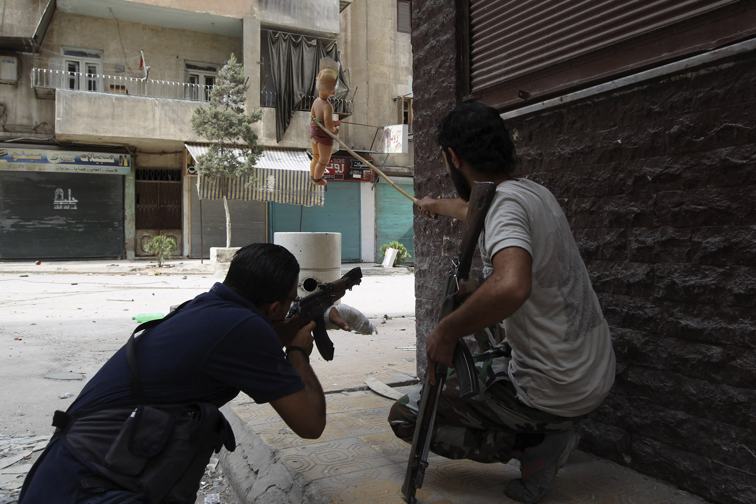 Sept. 18, 2013. A Kurdish Free Syrian Army fighter holds out a doll while his fellow fighter takes shooting position in Ashrafieh, Aleppo, Syria.