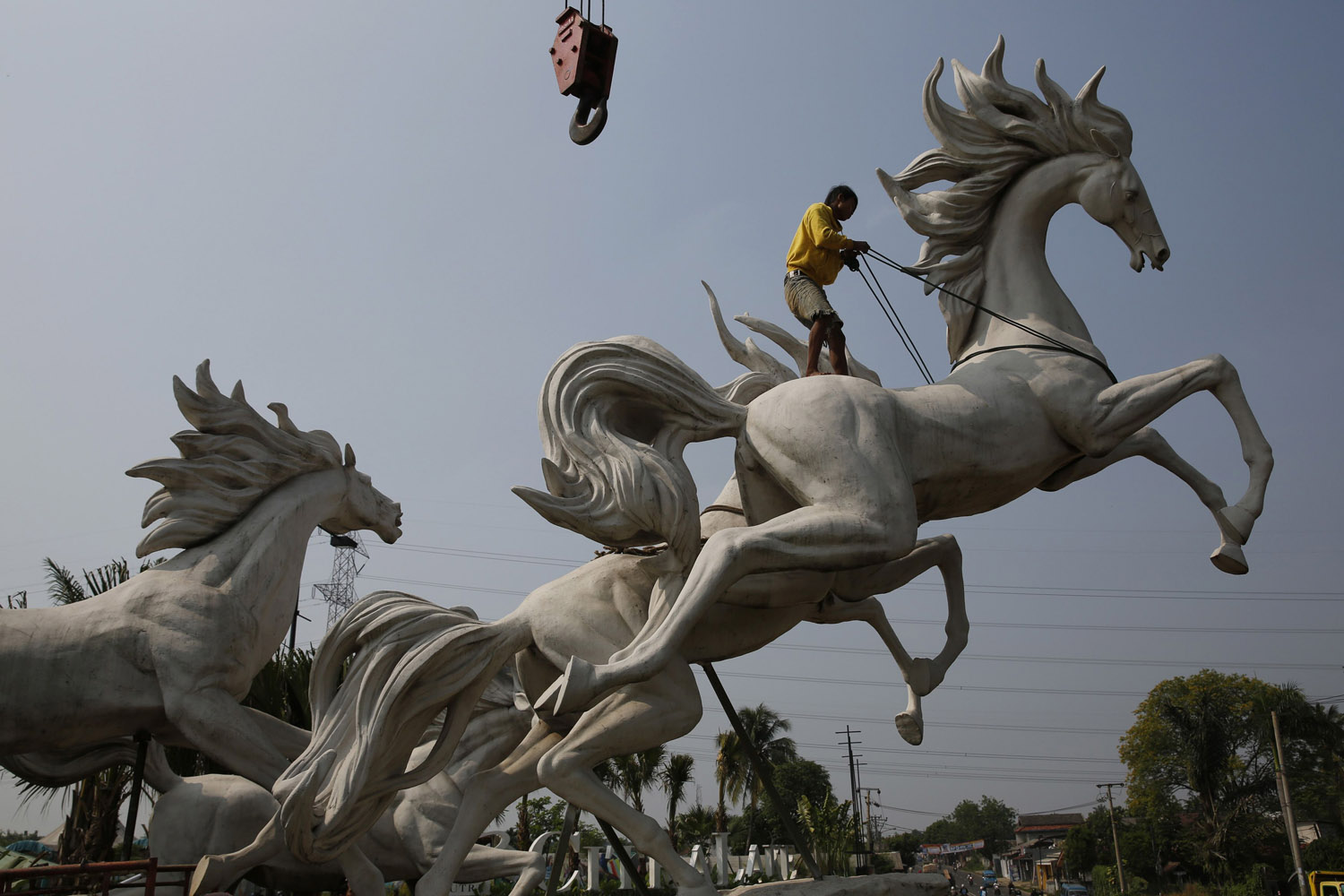 Sept. 19, 2013. A worker tightens a rope to raise a four-metre-high (13 ft) statue of horses at a new housing complex at Parung village in Bogor, Indonesia's West Java province.