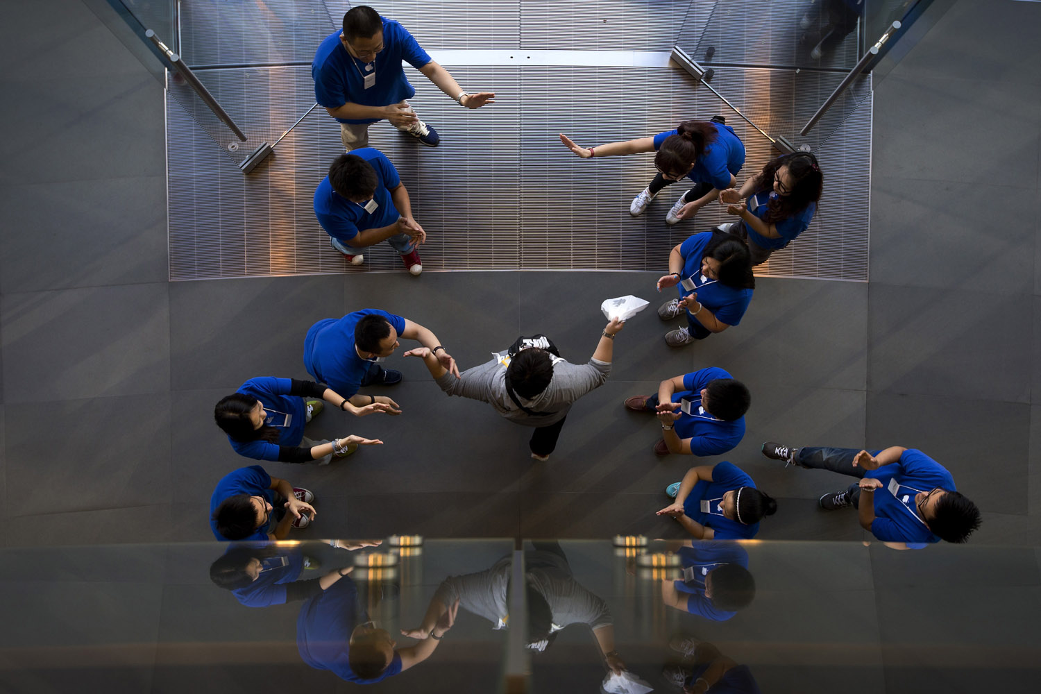 Sept. 20, 2013. Chinese employees cheer a customer after he bought new iPhone at an Apple store in Wangfujing shopping district in Beijing.