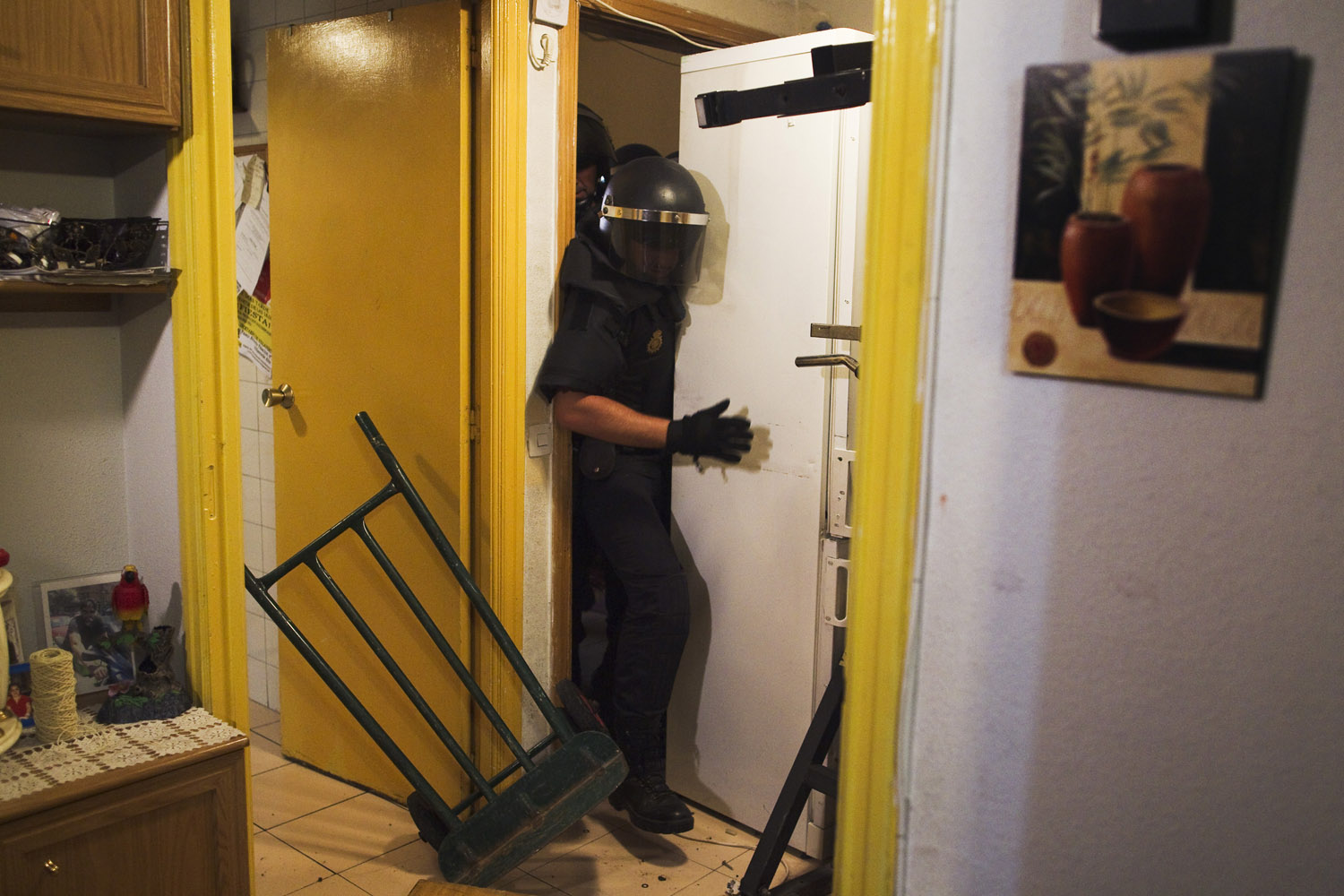 Sept. 25, 2013. Police remove the door and push away a refrigerator as they break into Maria Isabel Rodriguez Romero's apartment to evict her and her family in Madrid, Spain.