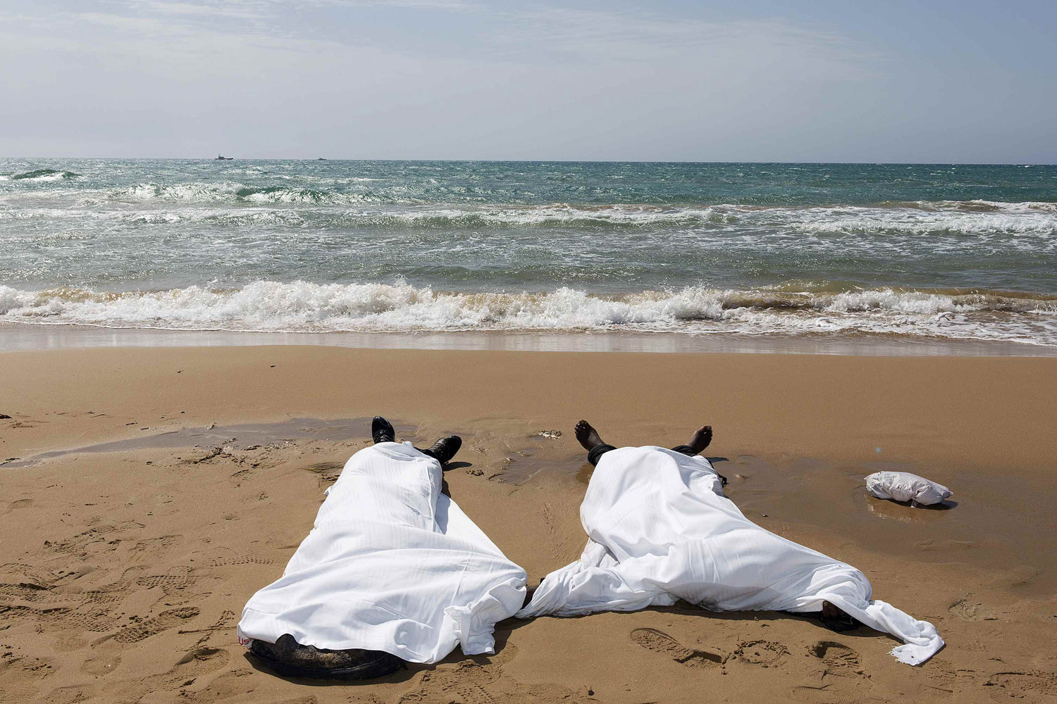 Sept. 30, 2013. Bodies of migrants who drowned lie on the beach in the Sicilian village of Sampieri in Italy.
