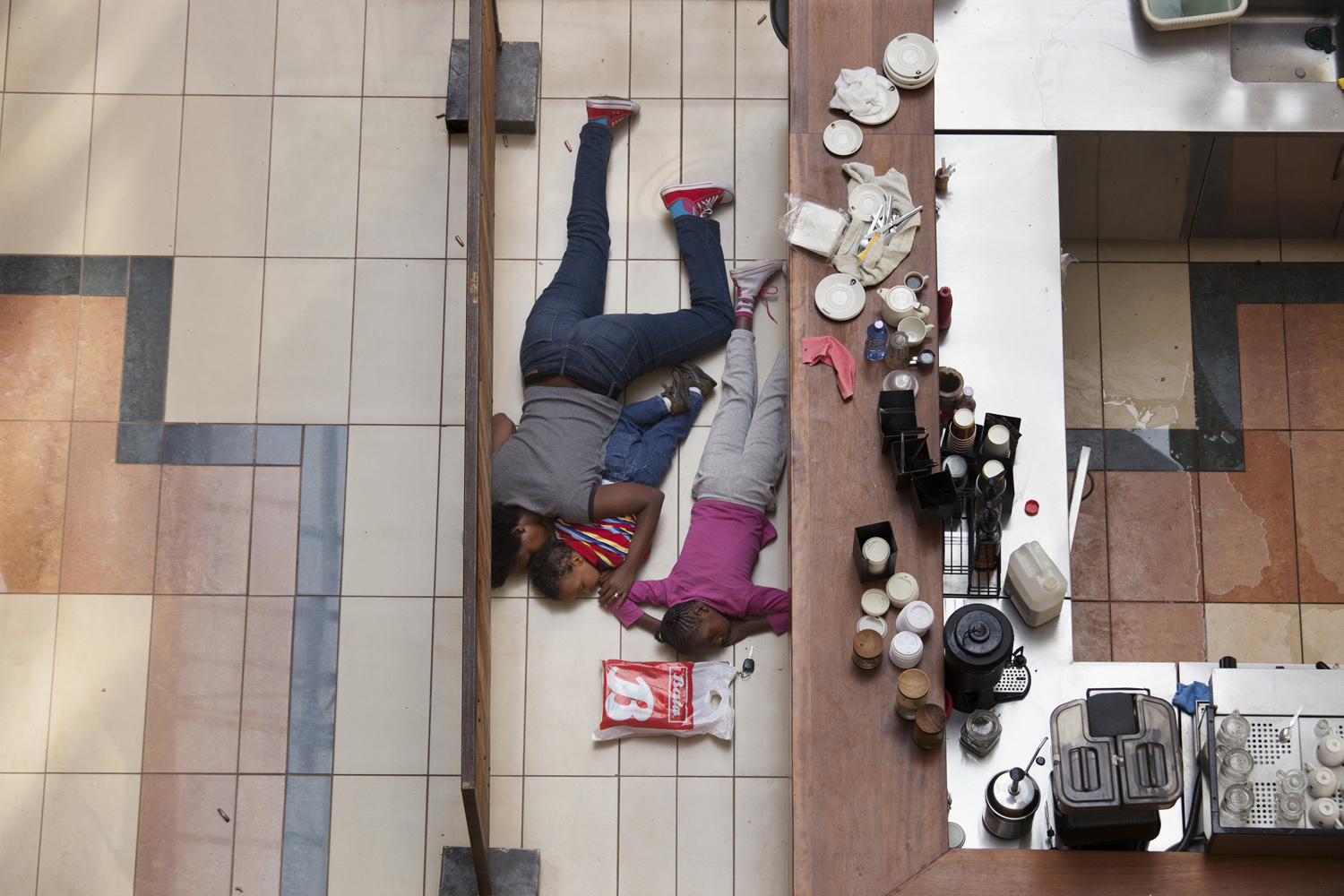 Sept. 21, 2013. A woman and children hide inside Westgate Mall in Nairobi, Kenya after a group of armed men attacked the upscale shopping center, killing at least 59 people and wounding at least 175.