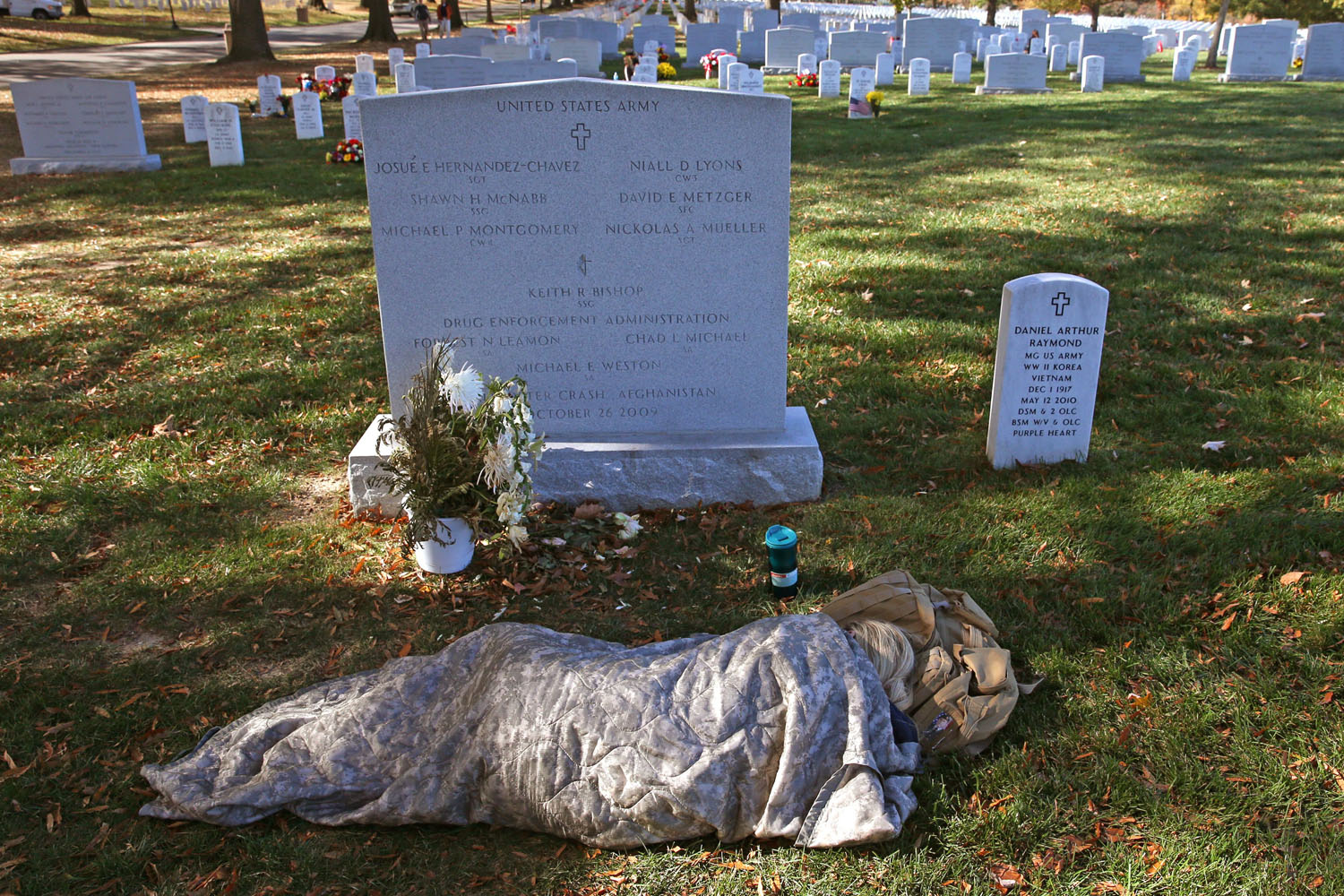 Nov. 11, 2013. Sarah Stanczyk lays covered up at the gravesite of her husband, SFC David Metzger, who was killed in Afghanistan in 2009, at Section 60 in Arlington Cemetery on Veterans Day.