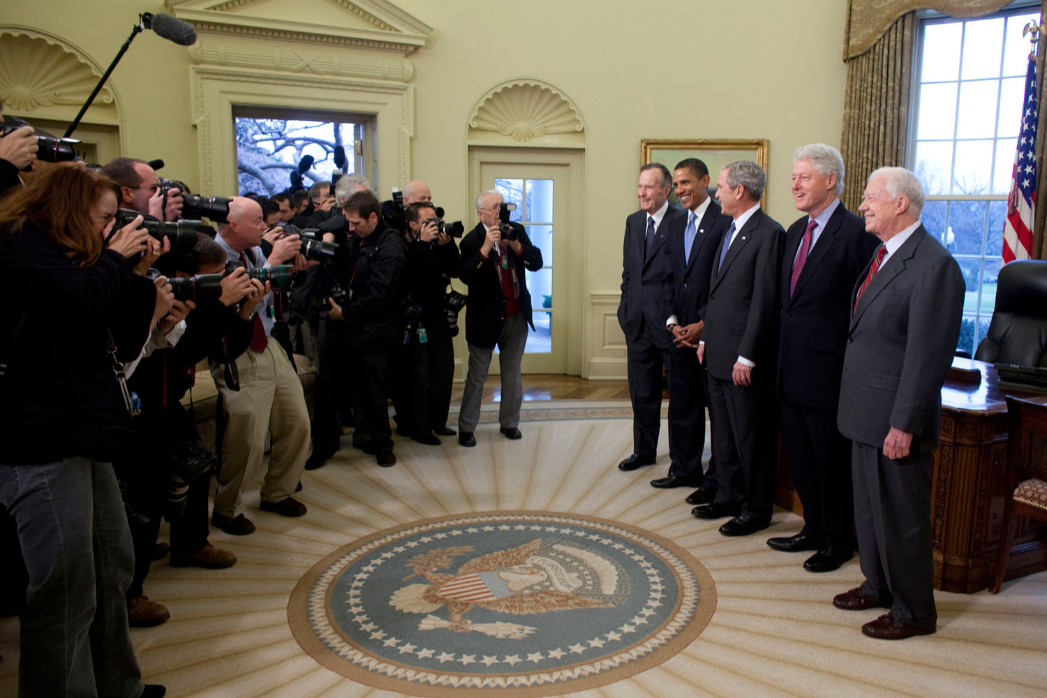 Photographers gather around President George W. Bush, President George H.W. Bush, President-elect Barack Obama, President Bill Clinton, and President Jimmy Carter, January 7, 2009.