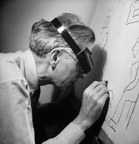 James Thurber draws with a tremulous hand on large sheets of yellow paper. Powerful watchmaker's magnifier helps his good eye to see what he is doing.
