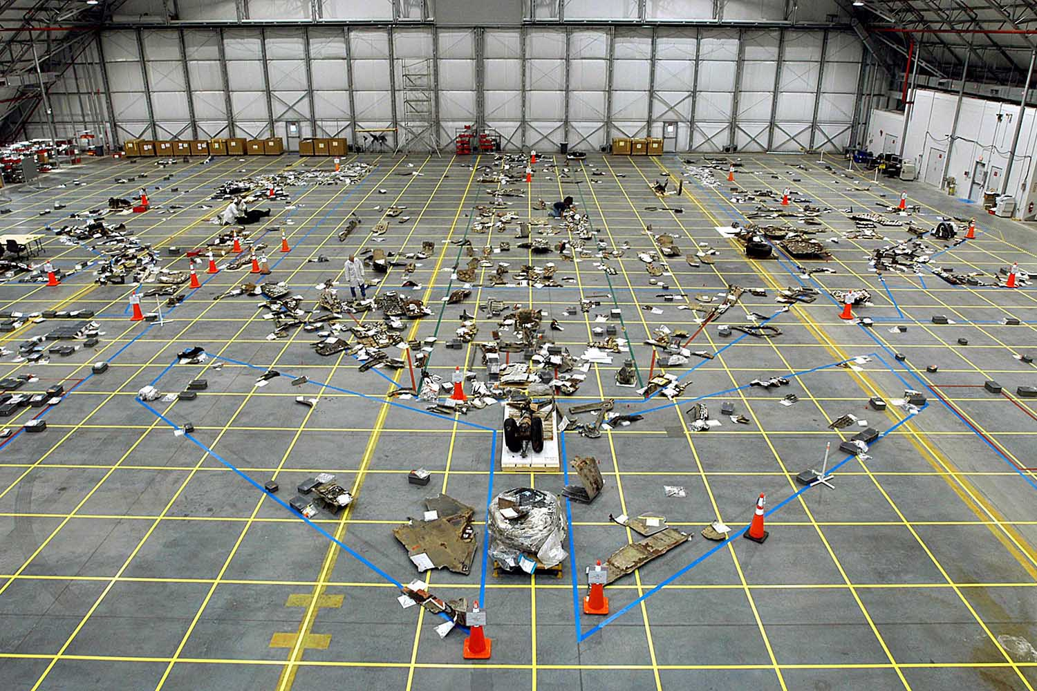 March 13, 2003. This photo provided by NASA on Feb. 1, 2013, the 10th anniversary since the orbiter broke apart in the skies over Texas, shows the RLV Hangar where the floor grid is marked with a growing number of pieces of the Columbia Space Shuttle debris.