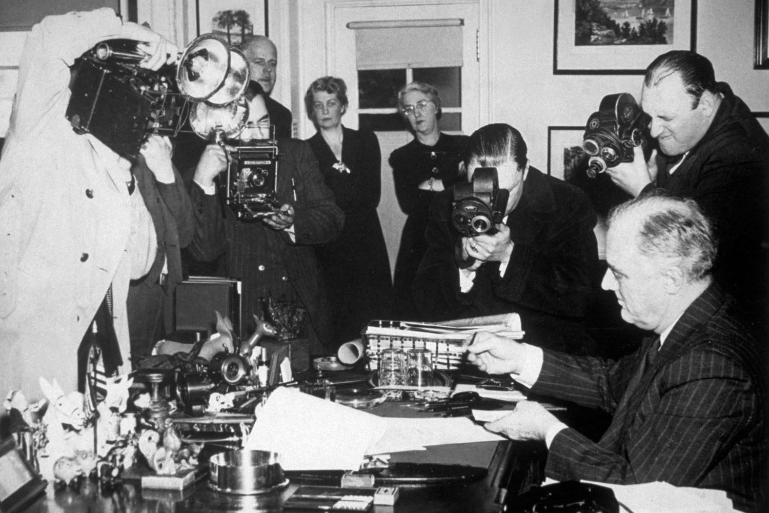 President Franklin D. Roosevelt, surrounded by photographers, signs the Lease-Lend Bill at the White House, March 11, 1941.